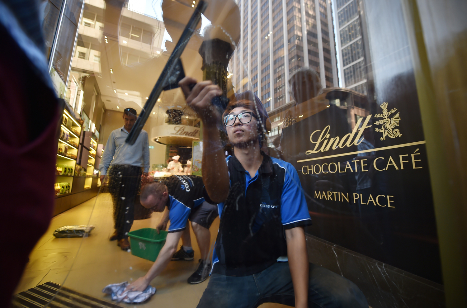 A staff member cleans the front door windows ahead of the re-opening of the Lindt Cafe at Martin Place in Sydney on March 20, 2015.