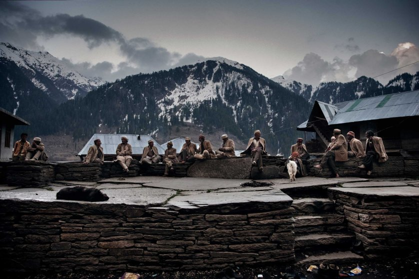 Elder men in the traditional wool suit sit in the village square near the temple. They are the first generation of people who started to cultivate the infesting strain that was growing wild in the Himalayas