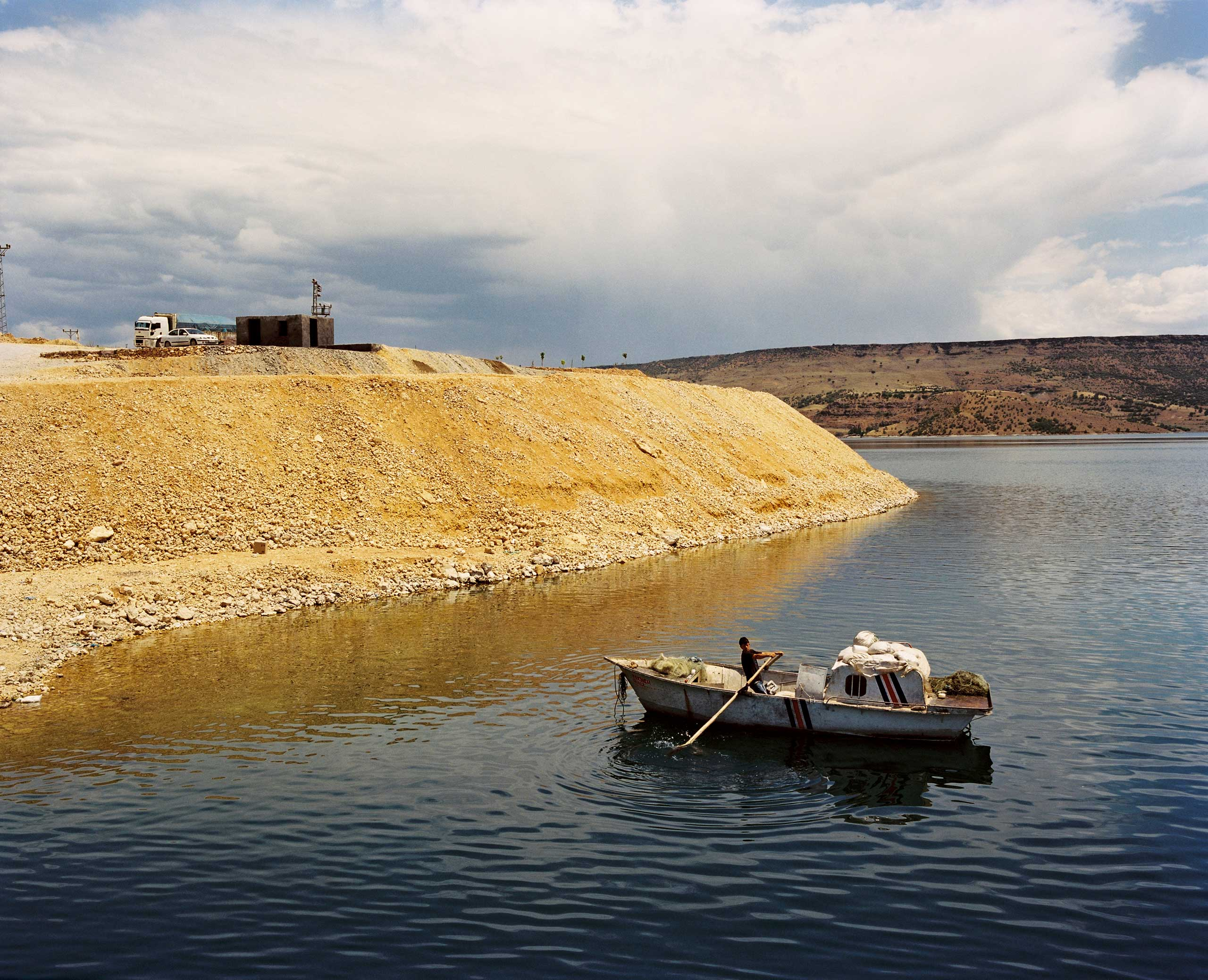 A man paddles in a boat across the Euphrates River near the hydroelectric Keban Dam. Turkey.
