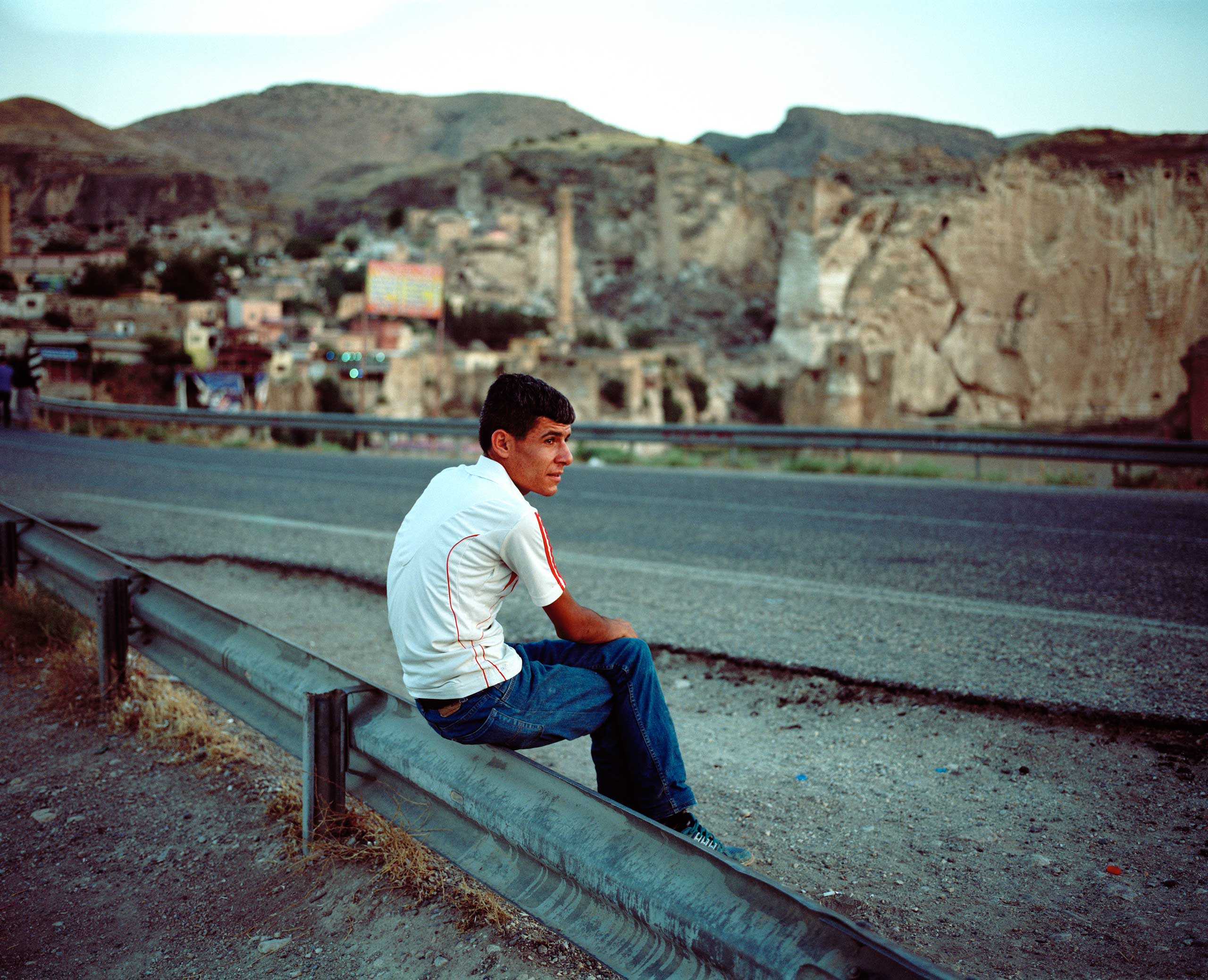 A man sits by the road along the bridge leading to Hasankeyf over the Tigris River. Hasankeyf, Turkey.