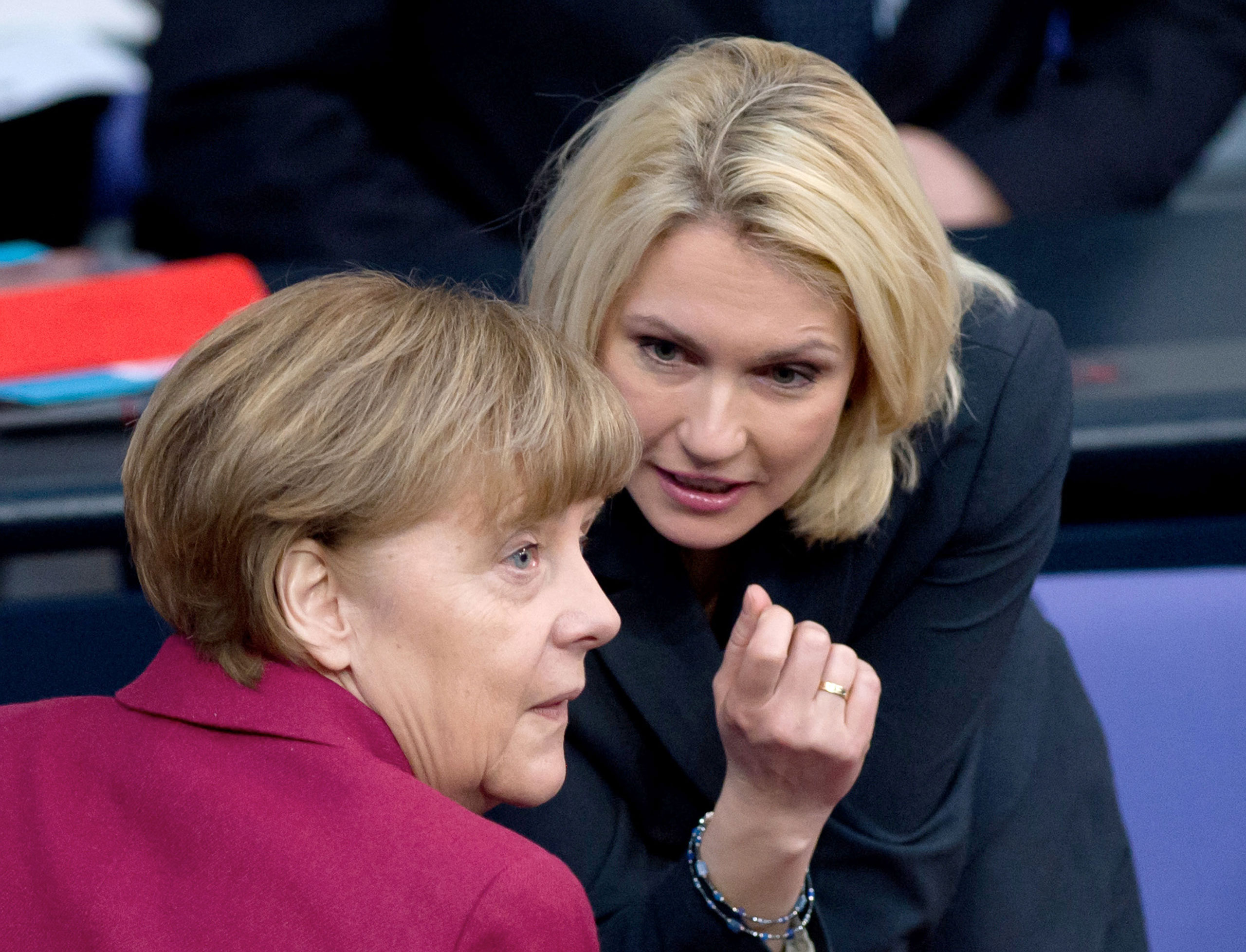 German chancellor Angela Merkel, left, and German Minister of Family Affairs Manuela Schwesig talk during a session of parliament in Berlin, March 6, 2015.
