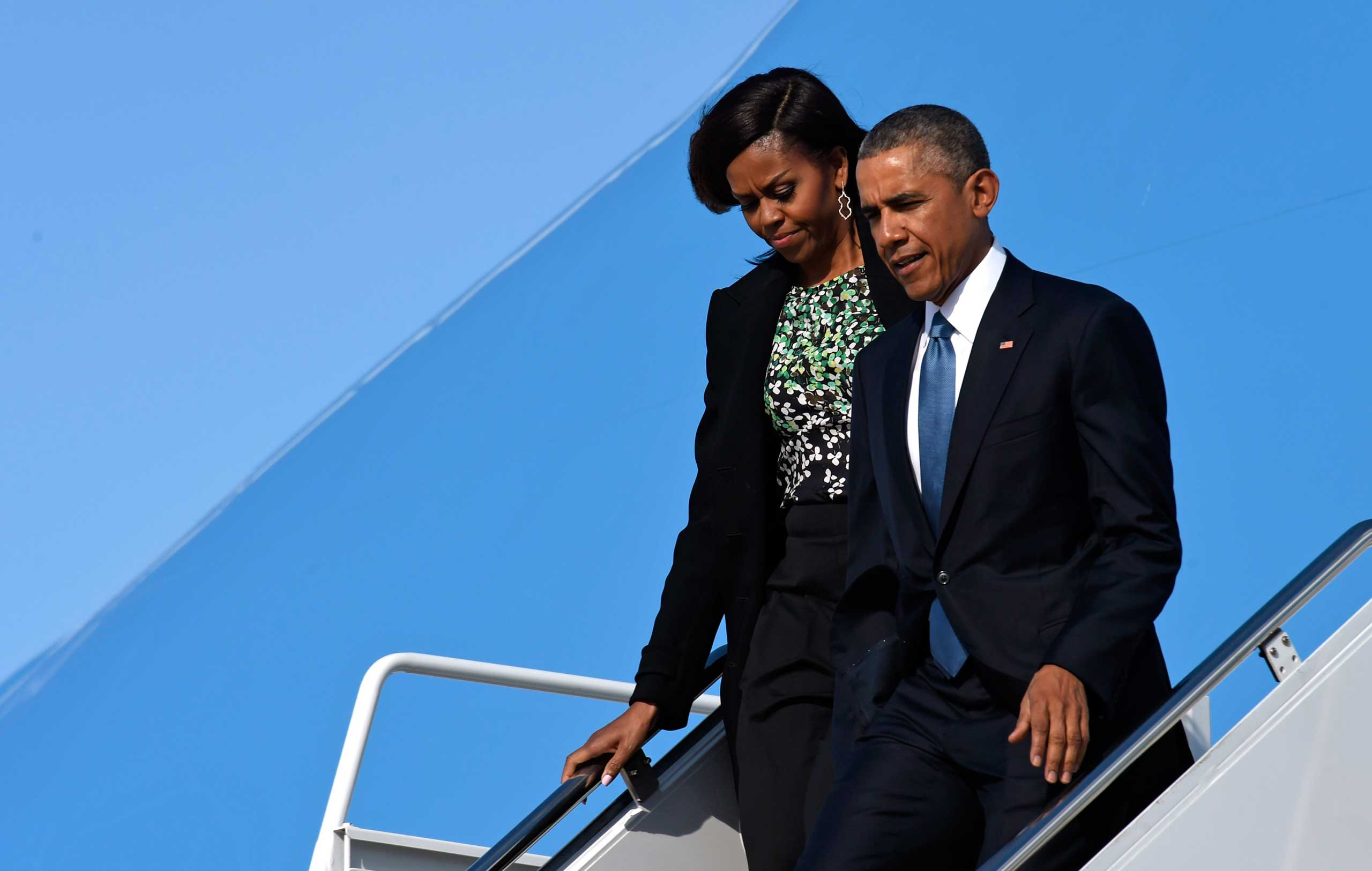 U.S. President Barack Obama and First Lady Michelle Obama walk down the steps of Air Force One at Andrews Air Force Base in Maryland on March 30, 2015