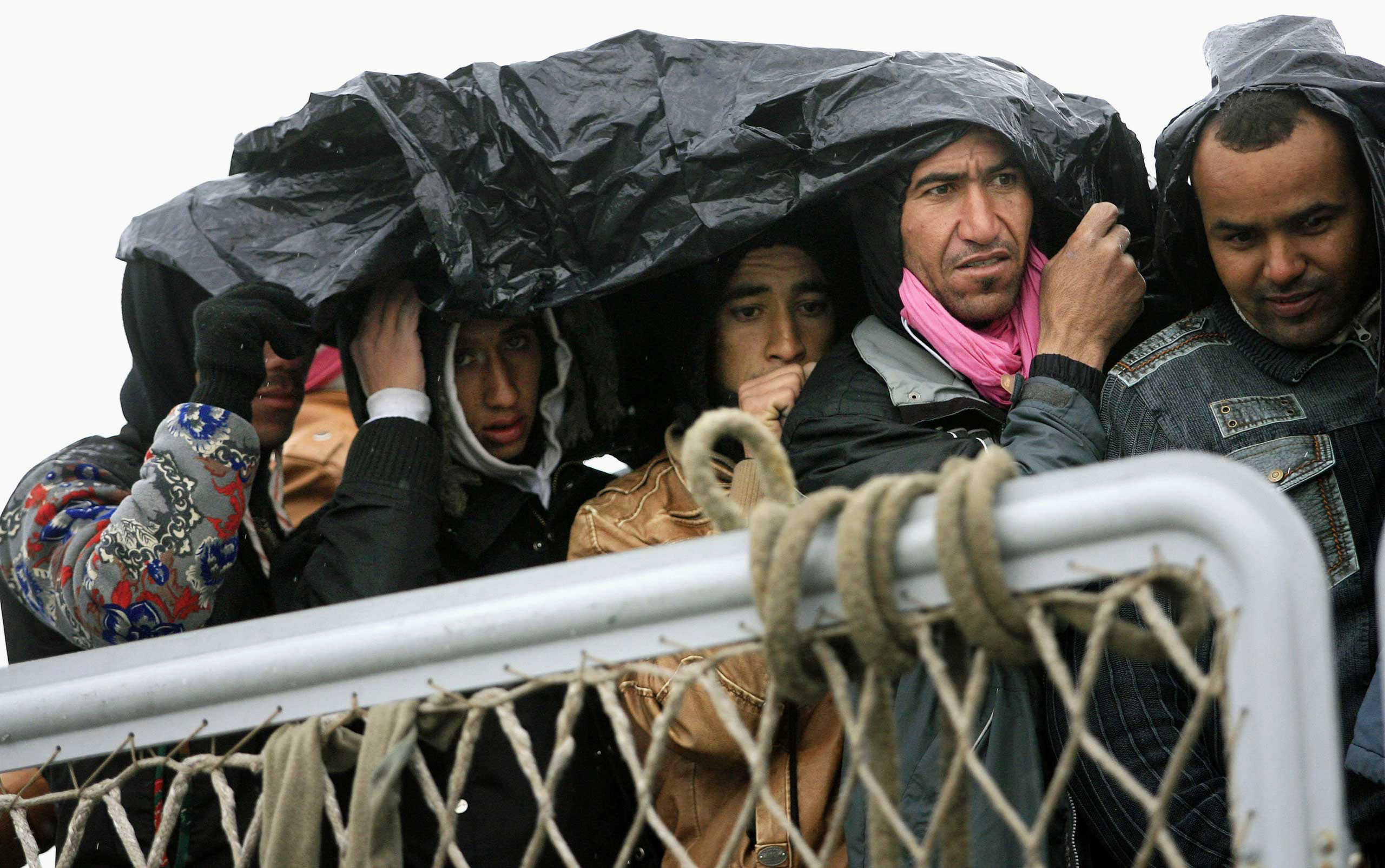 Migrants protect themselves from the rain as they wait to disembark from a ship on Feb. 17, 2015 in Porto Empedocle, south Sicily, following a rescue operation of migrants as part of the International Frontex plan.