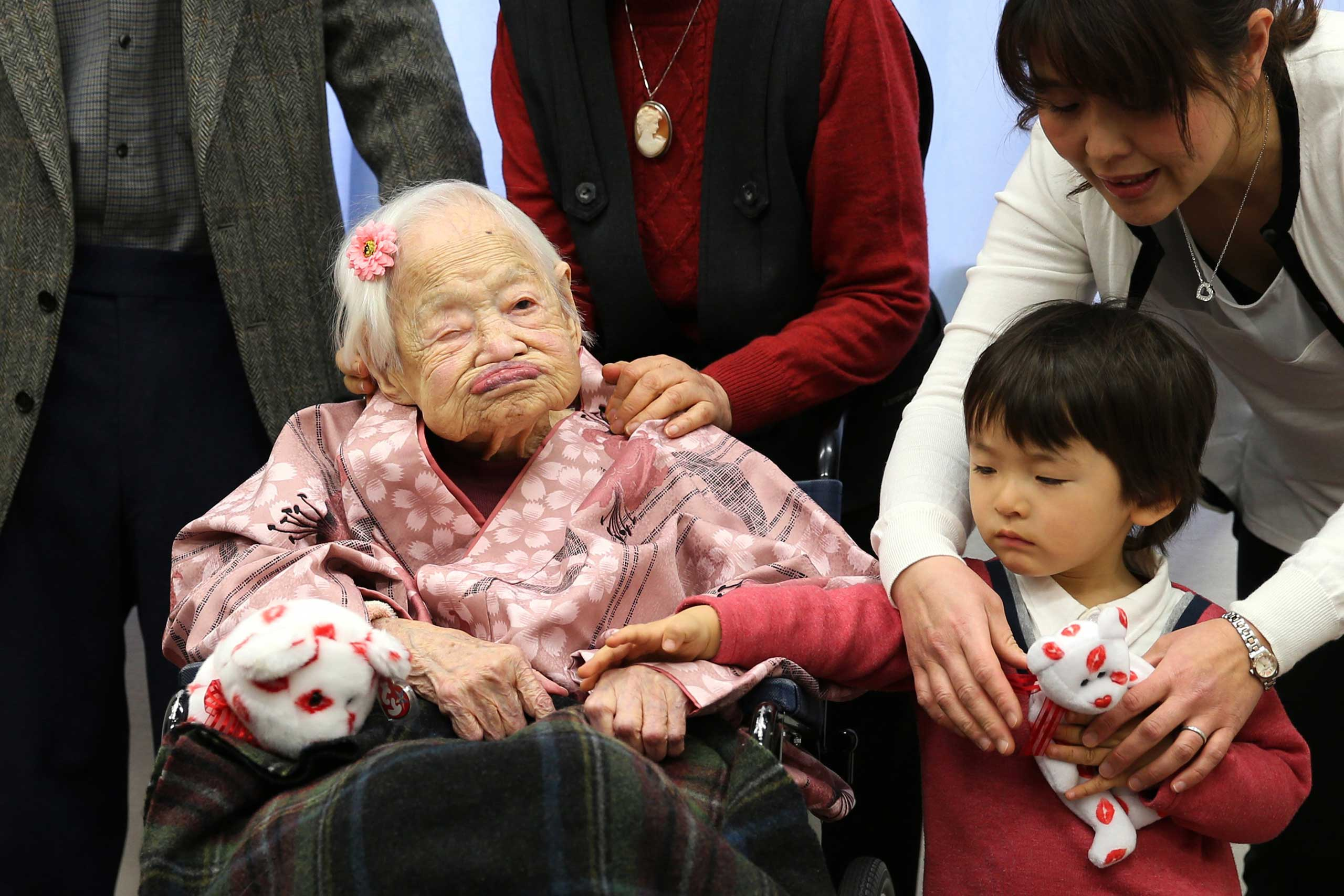 Misao Okawa, the world's oldest Japanese woman poses for a photo with her great-grandchild Himaki and grandchild Takako Okawa on her 117th birthday celebration at Kurenai Nursing Home on March 4, 2015 in Osaka, Japan.