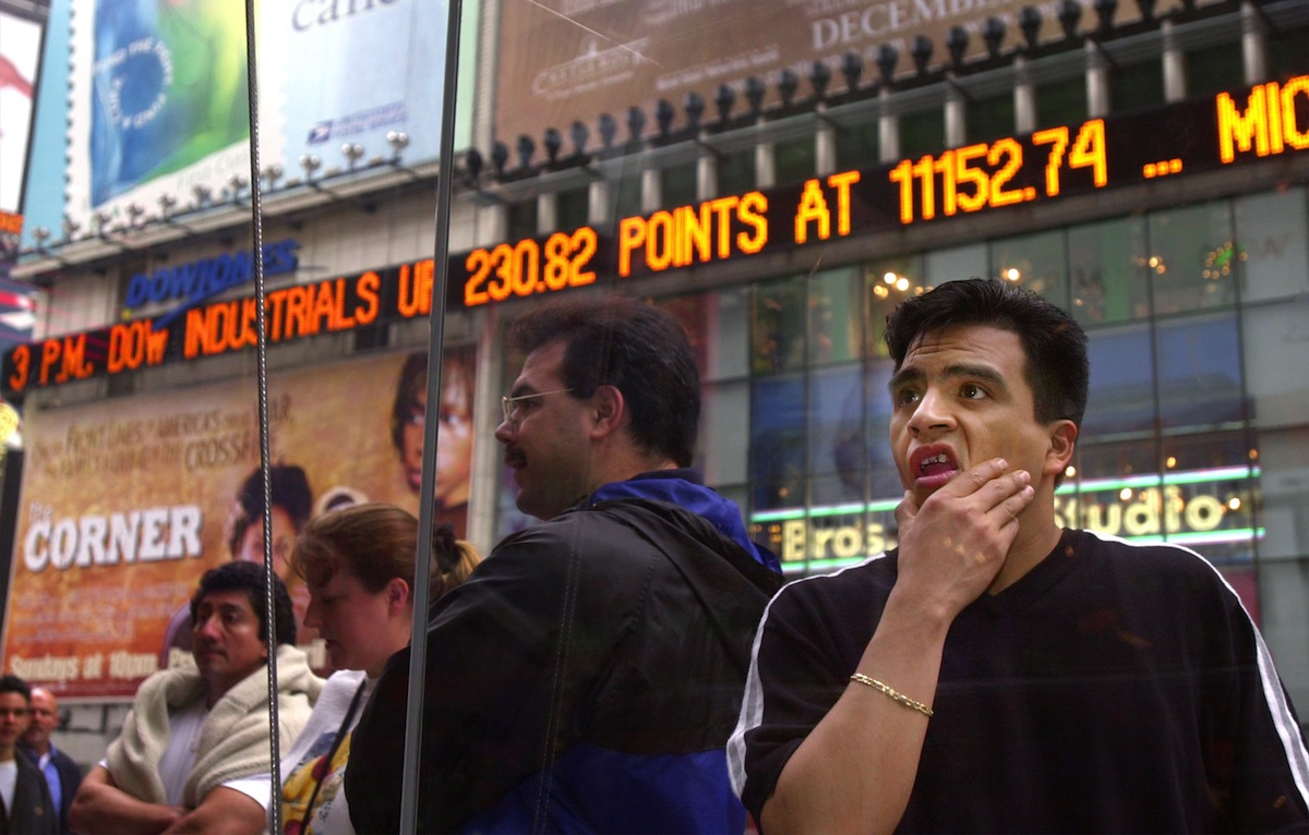 A passer-by looks over the prices on the Nasdaq board in Times Square in New York, April 3, 2000.