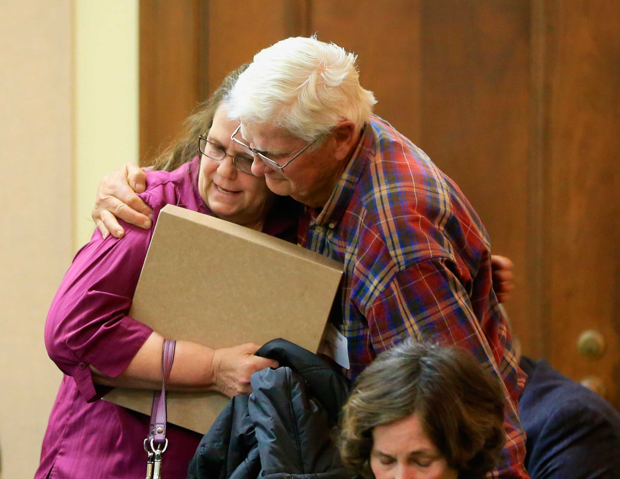 Miriam Thimm Kelle, left, whose brother James Thimm was tortured and killed on a southeast Nebraska farm in 1985, is hugged by Byron Peterson of Scottsbluff, after she testified in favor of a law proposal to change the death penalty to life imprisonment without parole, during a hearing before the Judiciary Committee in Lincoln, Neb., March 4, 2015.