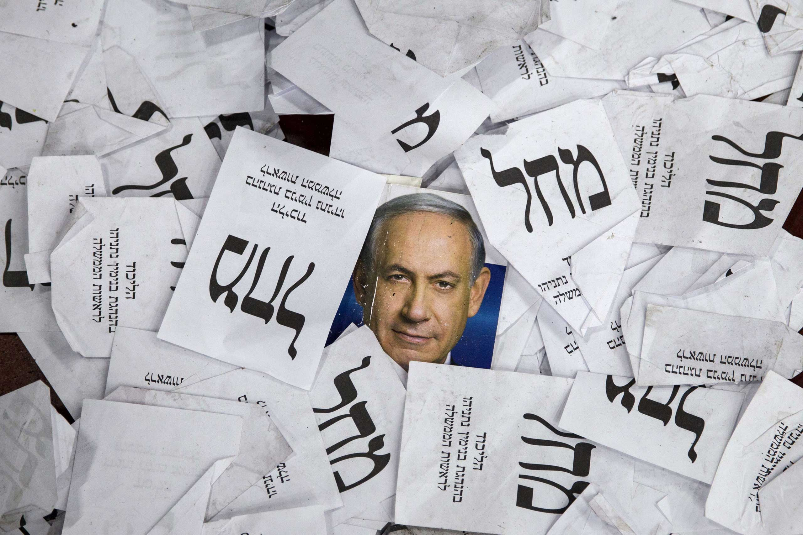 Copies of ballots papers and campaign posters for Israel's Prime Minister Benjamin Netanyahu's Likud Party lie on the ground in the aftermath of the country's parliamentary elections in Tel Aviv on March 18, 2015.