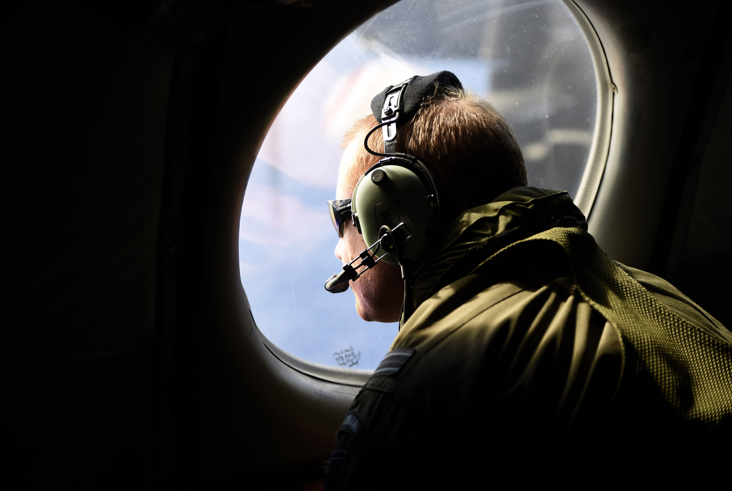 A crew member looks out an observation window aboard a Royal New Zealand Air Force P3 Orion maritime search aircraft as it flies over the southern Indian Ocean looking for debris from missing Malaysian Airlines flight MH 370 on April 11, 2014