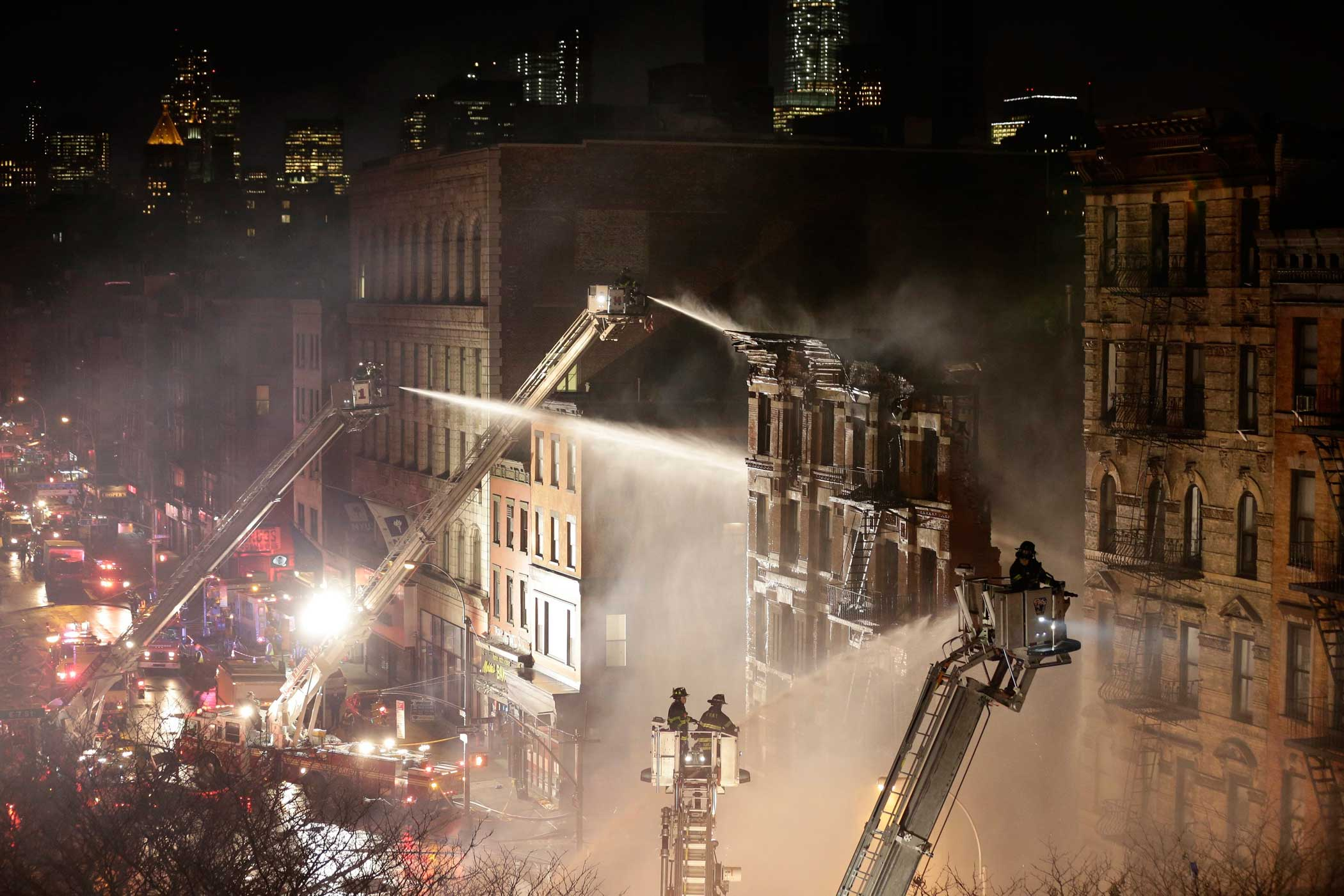 Firefighters respond to an explosion and partial building collapse in a residential and commercial mixed use multi-story structure in lower Manhattan, New York on March 26, 2015.