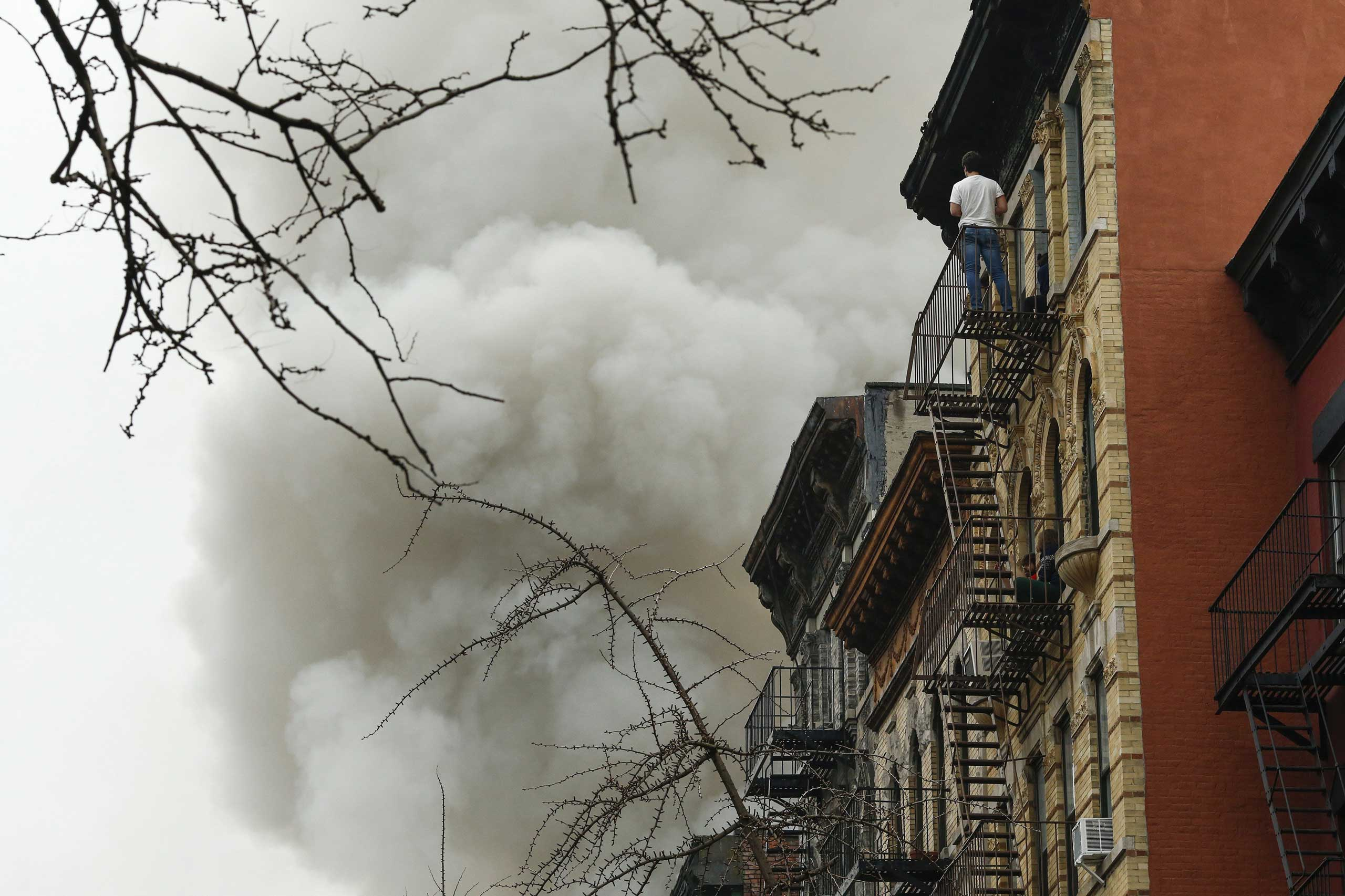 A resident watches a blaze at a commercial and residential block in New York City on March 26, 2015.