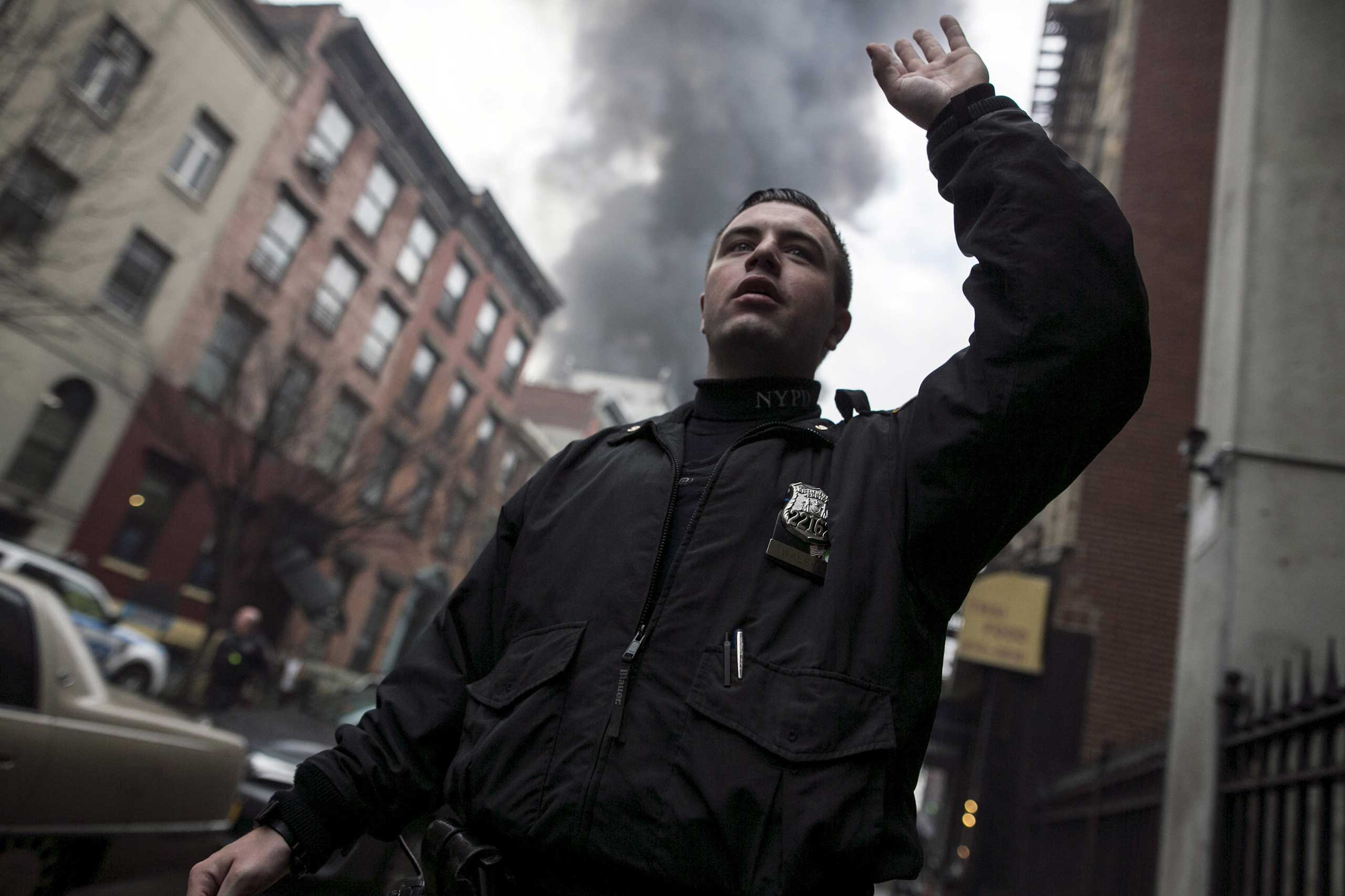 A New York Police Department (NYPD) officers signals residents away from the site of a building fire in the East Village neighborhood of New York City on March 26, 2015.
