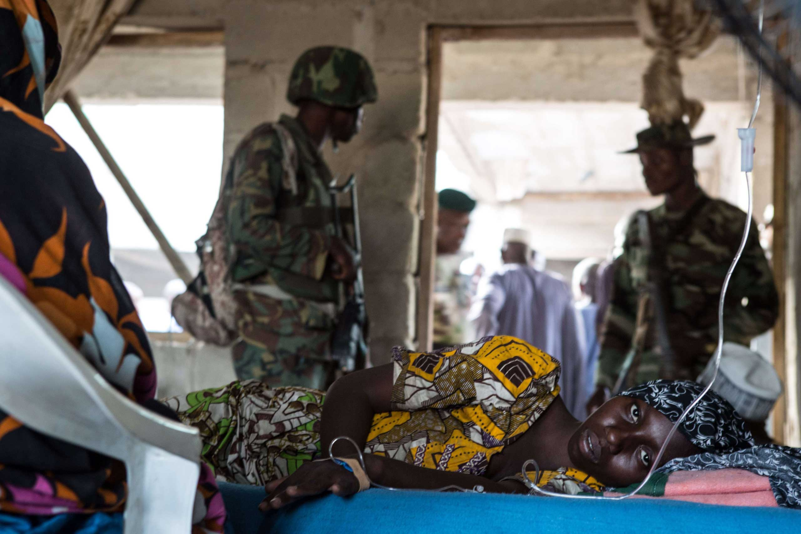 A young woman lies ill in a makeshift hospital room in Maiduguri, northwest of Bama on March 25, 2015.