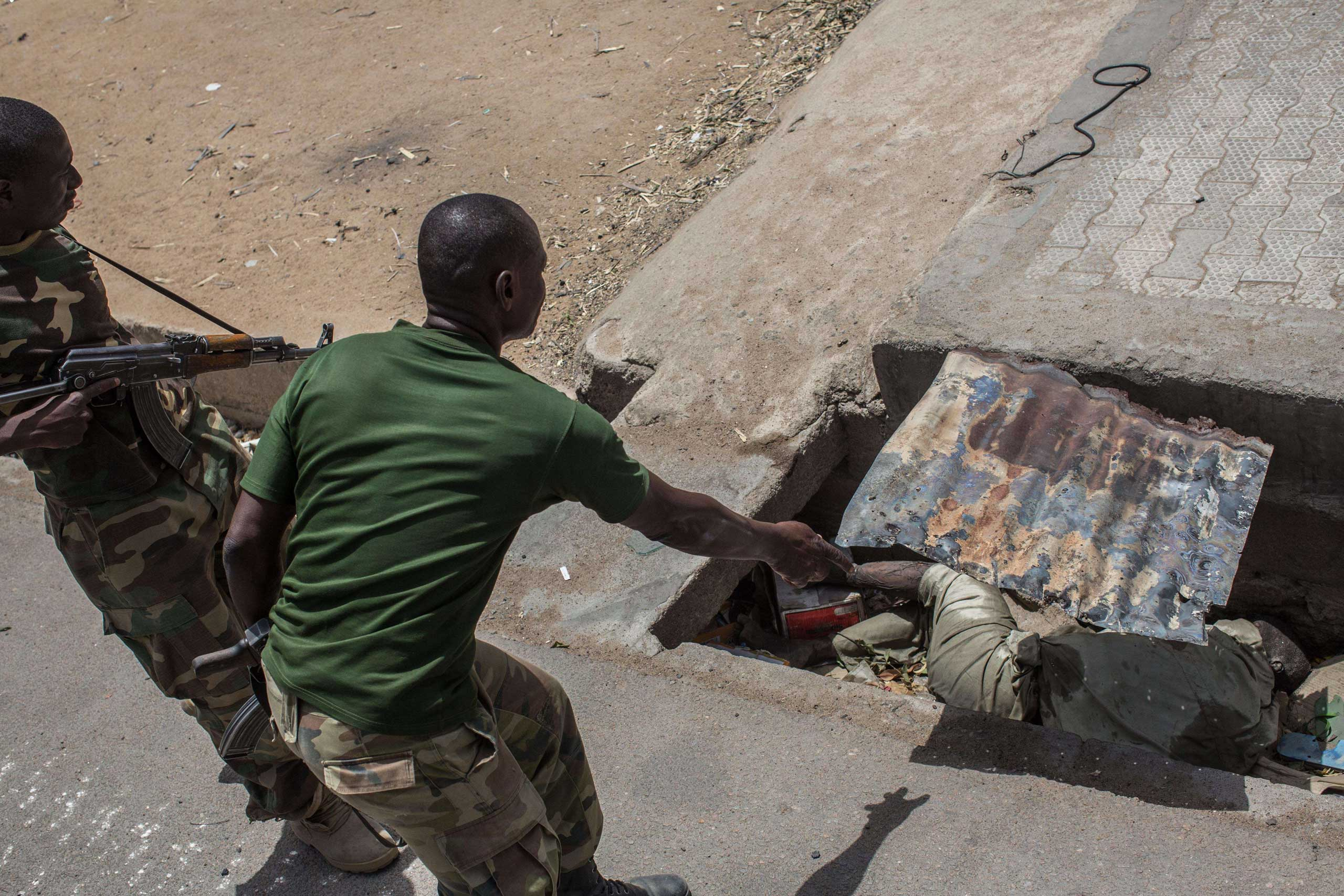 Members of the Nigerian army discover a body decomposing in a sewer in Bama on March 25, 2015.