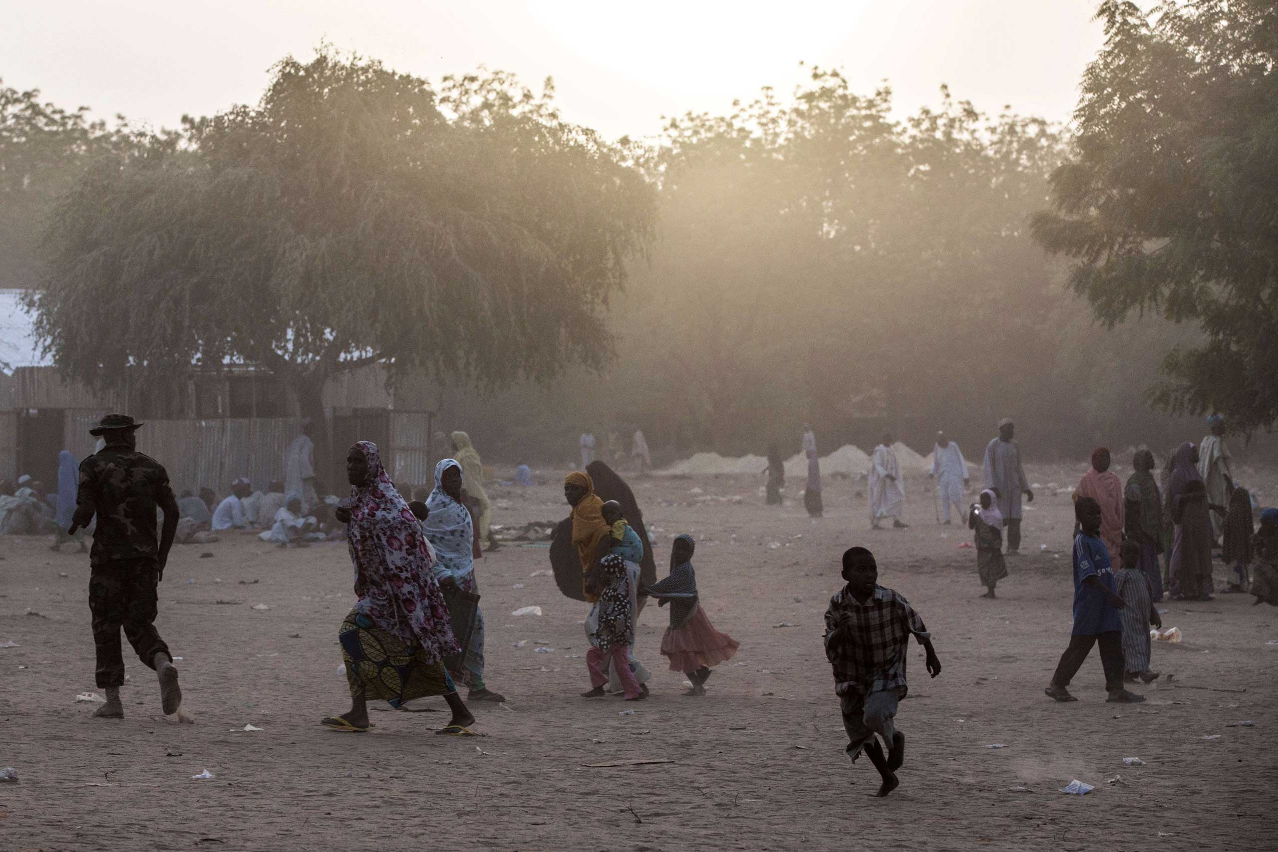 Civilians who fled the fighting in Bama and the surrounding areas in recent days walk at a makeshift camp for displaced people on the outskirts of Maiduguri, northwest of Bama on March 25, 2015.