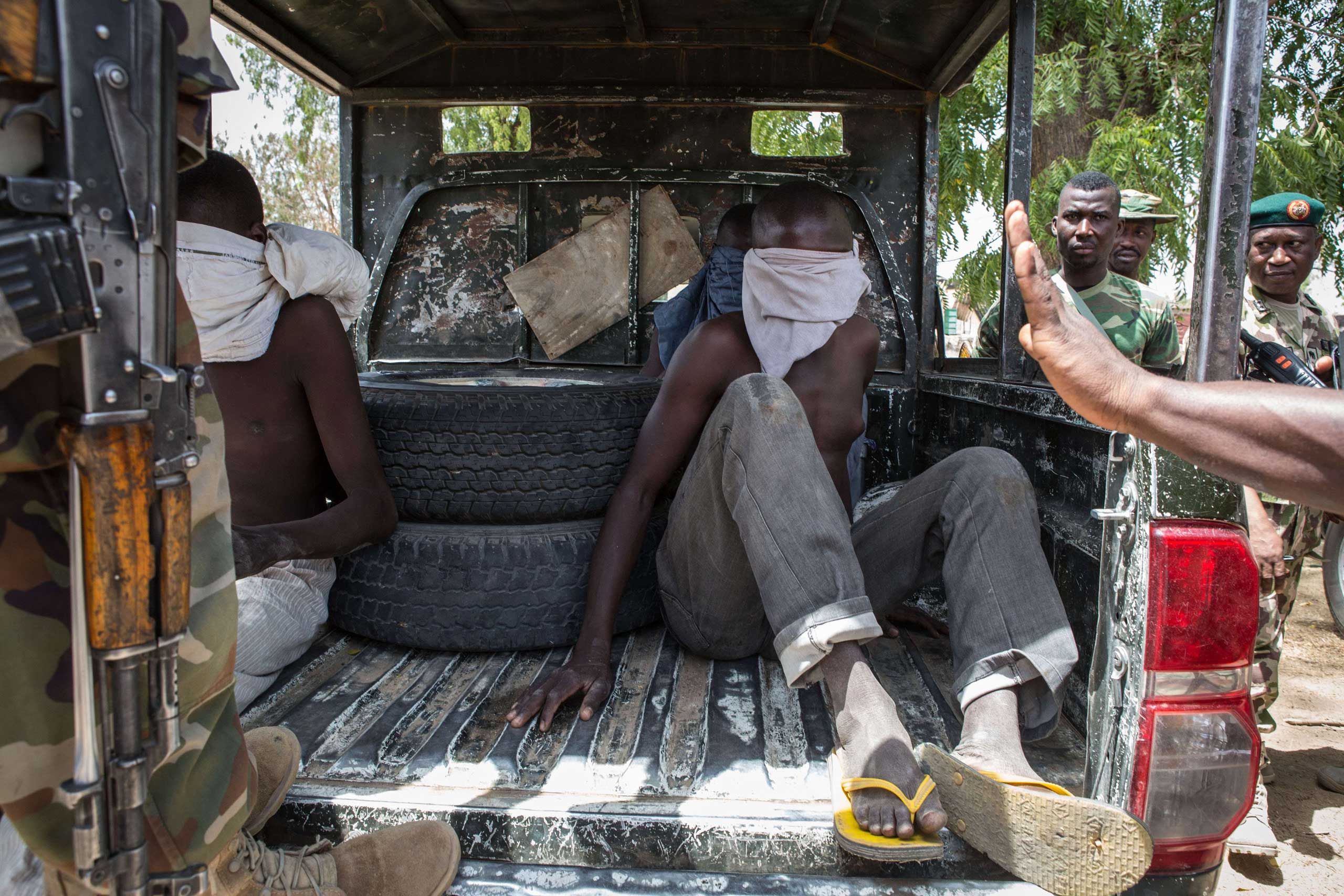 Three young men, who were discovered while entering Bama, sit blindfolded in the back of a pick-up truck before being taken for interrogation by the Nigerian army in Bama on March 25, 2015.
