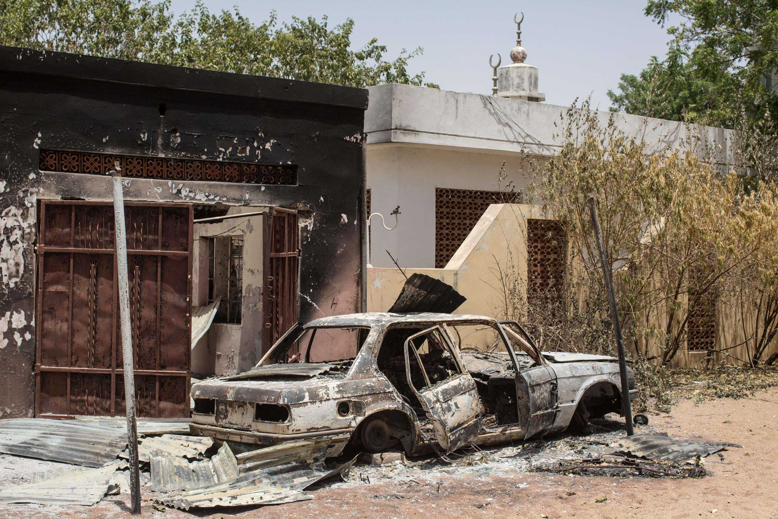 The wreckage of a burnt car sits outside the former emir's palace that was used by Boko Haram militants as a headquarters but was burned down when they fled Bama, March 25, 2015.