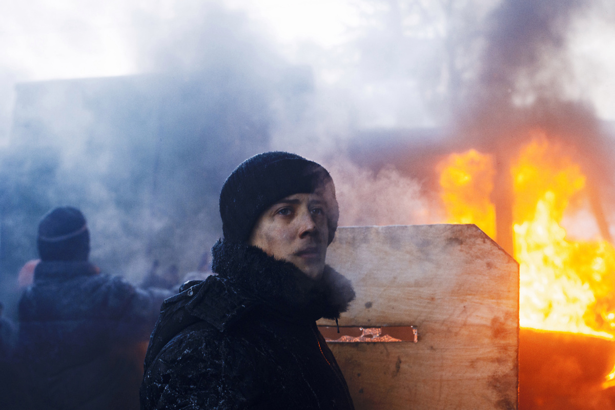 Jan. 24, 2014. A protestor holds a handmade shield as protection during rioting, Kiev, Ukraine