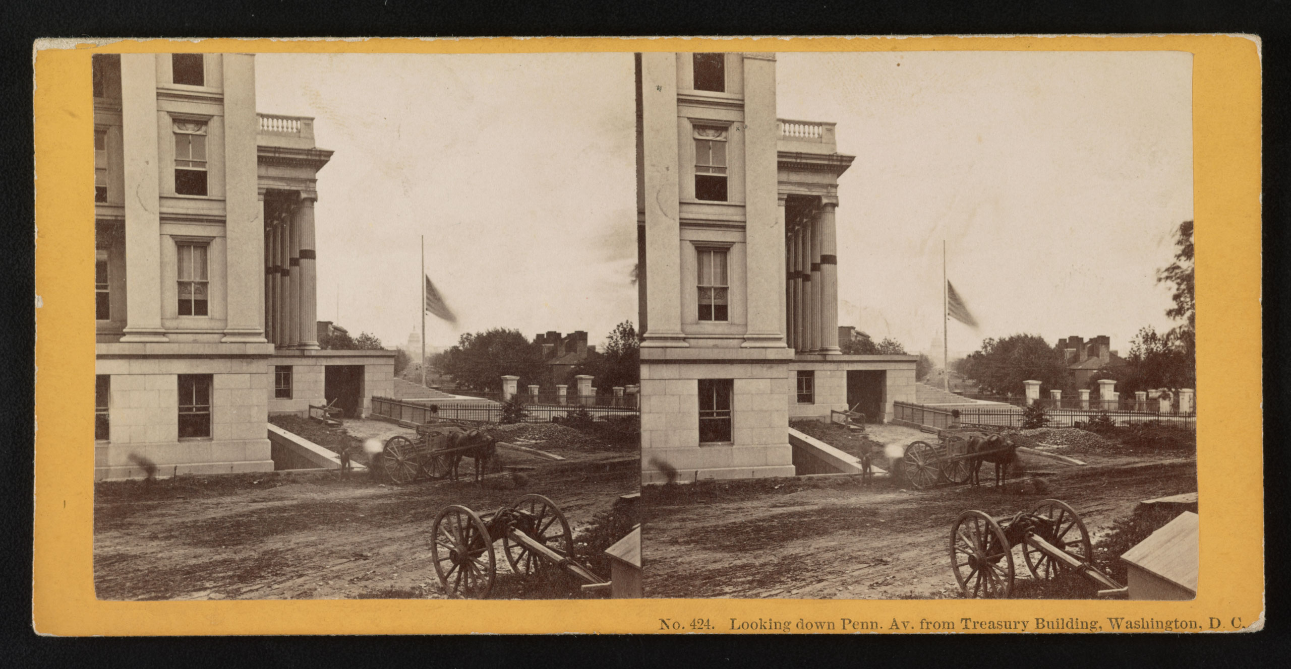 A view of Pennsylvania Avenue in Washington D.C. after the death of Abraham Lincoln showing mourning bands draped on columns, and a flag at half staff. A caisson is parked in the foreground, 1865.
