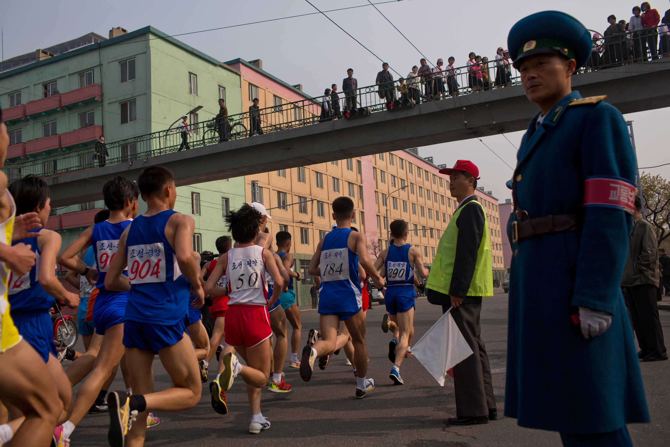 Runners pass under a pedestrian bridge during the running of the Mangyongdae Prize International Marathon in Pyongyang, North Korea on April 13, 2014.