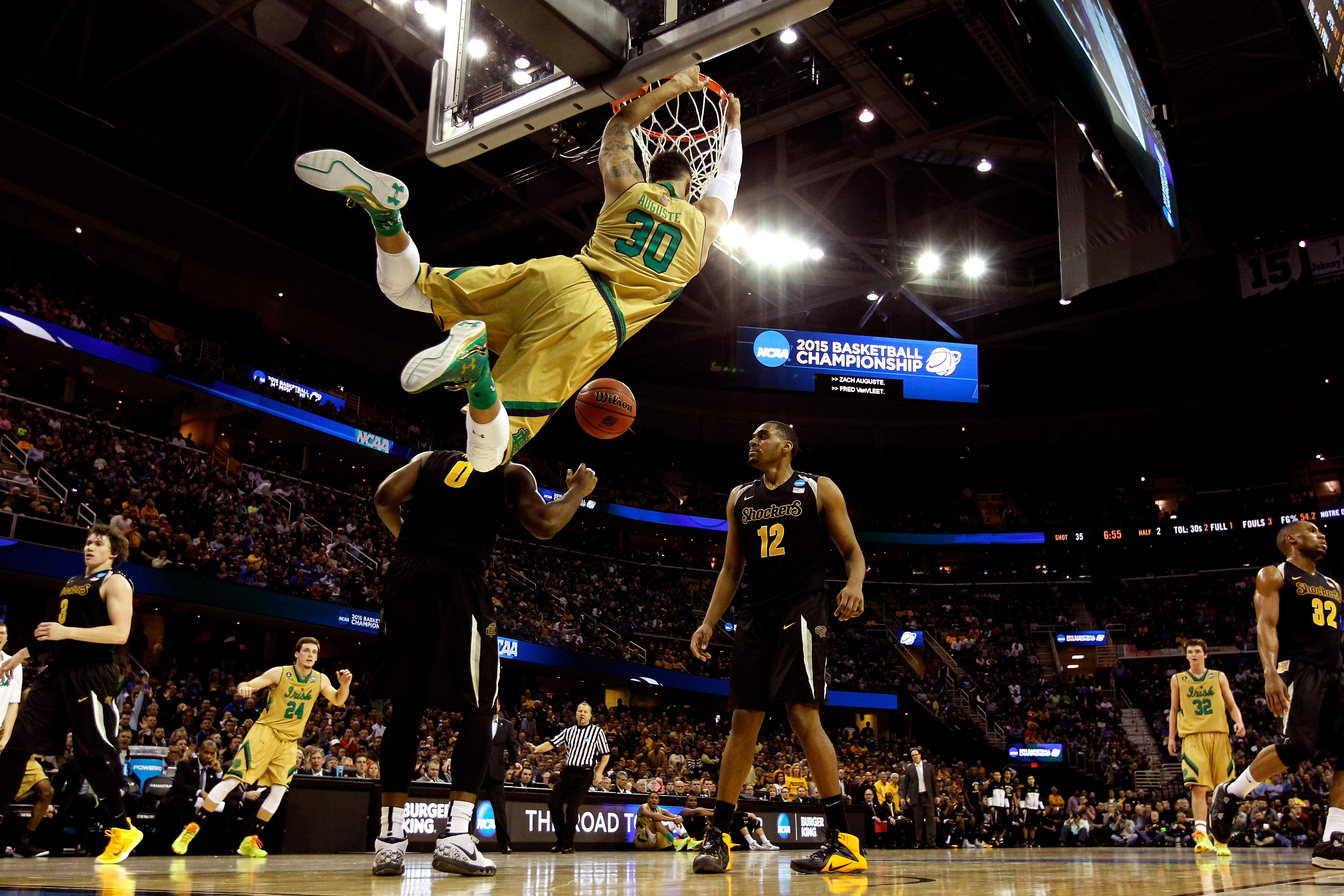 Zach Auguste #30 of the Notre Dame Fighting Irish dunks in the second half against Rashard Kelly #0 and Darius Carter #12 of the Wichita State Shockers during the Midwest Regional semifinal of the 2015 NCAA Men's Basketball Tournament at Quicken Loans Arena on March 26, 2015 in Cleveland, Ohio.