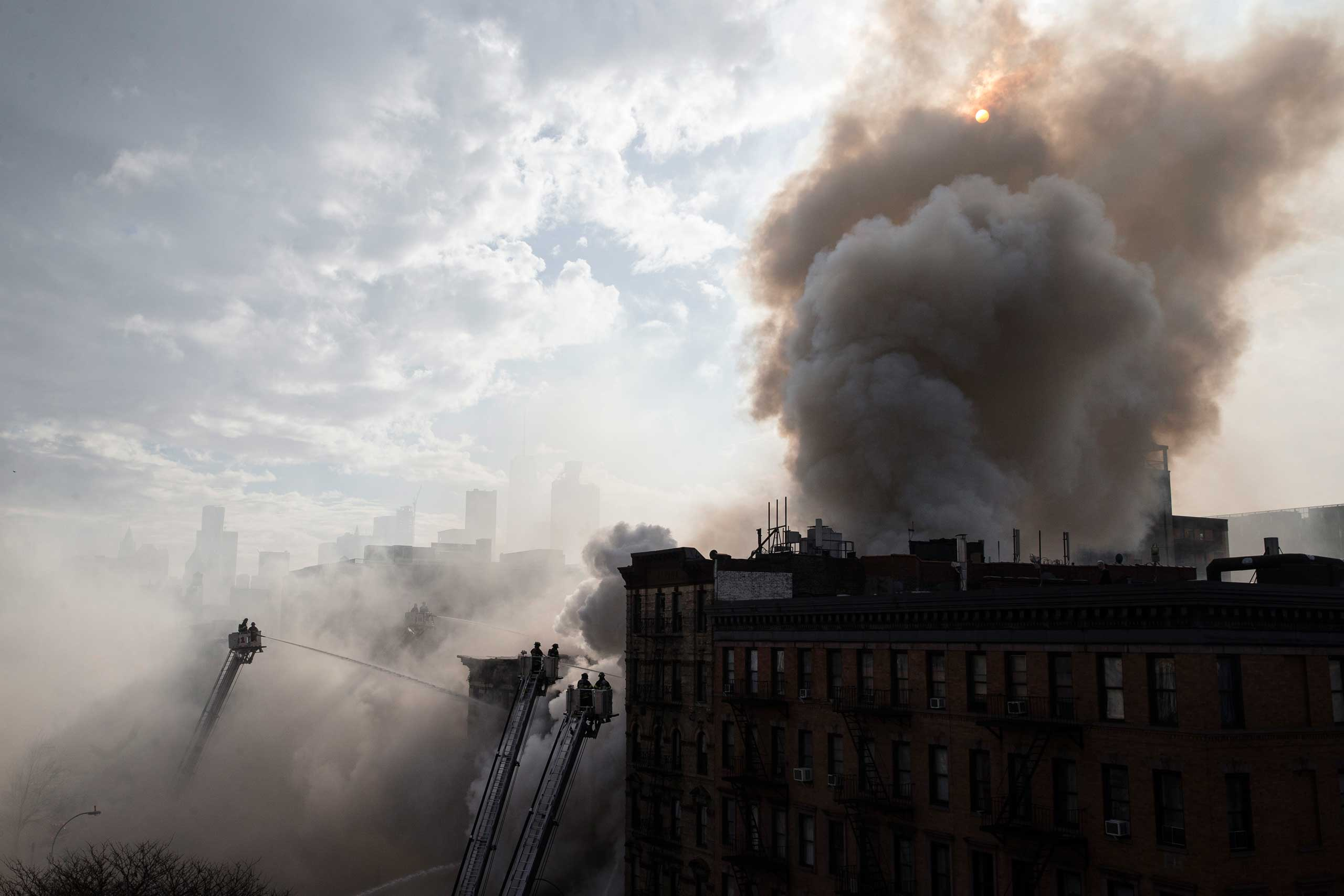 New York City firefighters work the scene of a large fire and a partial building collapse in the East Village neighborhood of New York City on March 26, 2015.