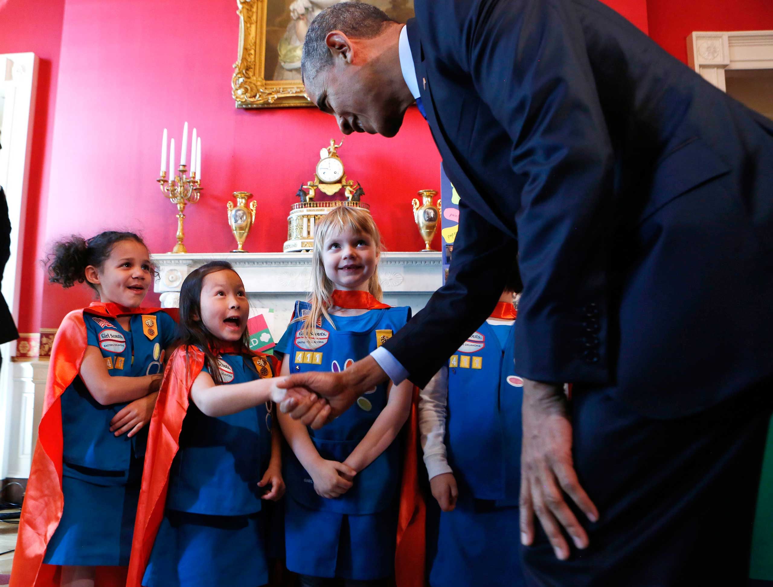 U.S. President Barack Obama (R) shakes hands with a group of  six-year-old Girls Scouts from Tulsa Oklahoma who designed a battery powered page turner to help people who are paralyzed or have arthritis at the 2015 White House Science Fair in Washington on March 23, 2015.