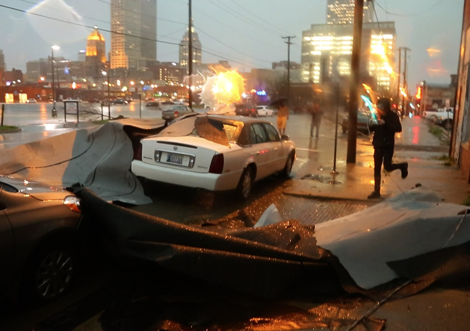 A man runs to his car after a roof fell on it near First and Greenwood in Tulsa, Okla., on March 25, 2015.
