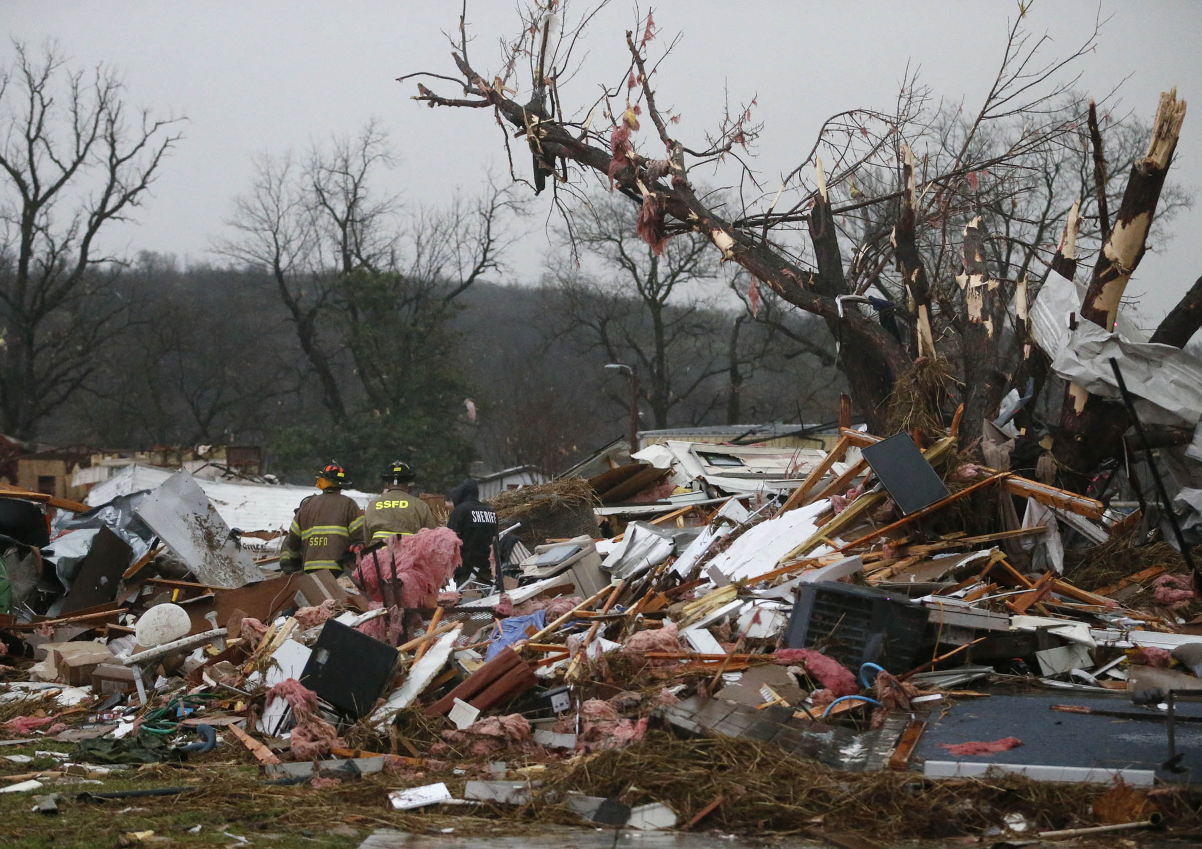 First responders work to free a man from a rubble pile after a round of severe weather hit a trailer park in Sand Springs, Okla., on March 25, 2015.