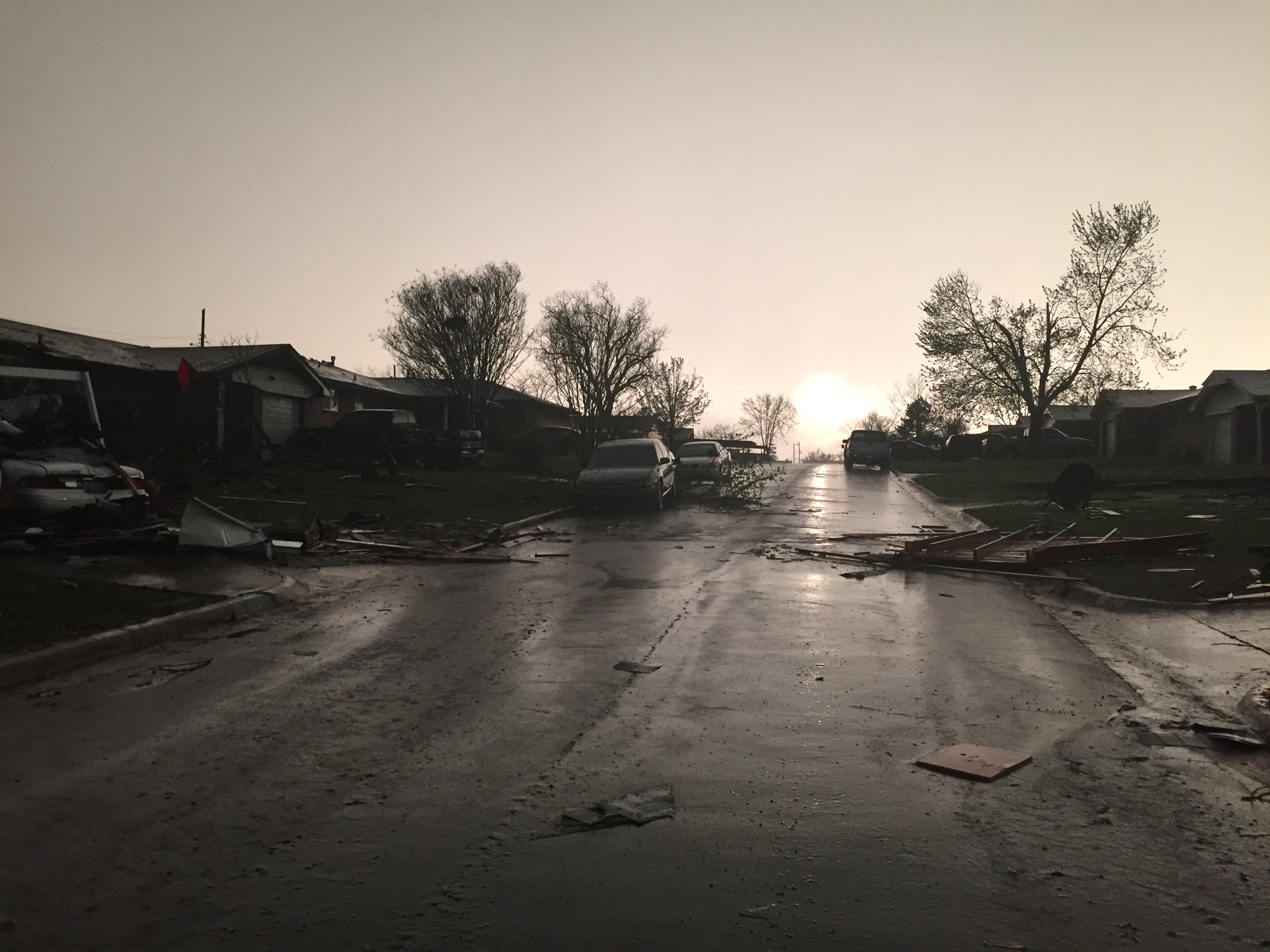 Debris and downed trees litter the streets after a tornado ripped through Moore, Okla. on March 25, 2015.