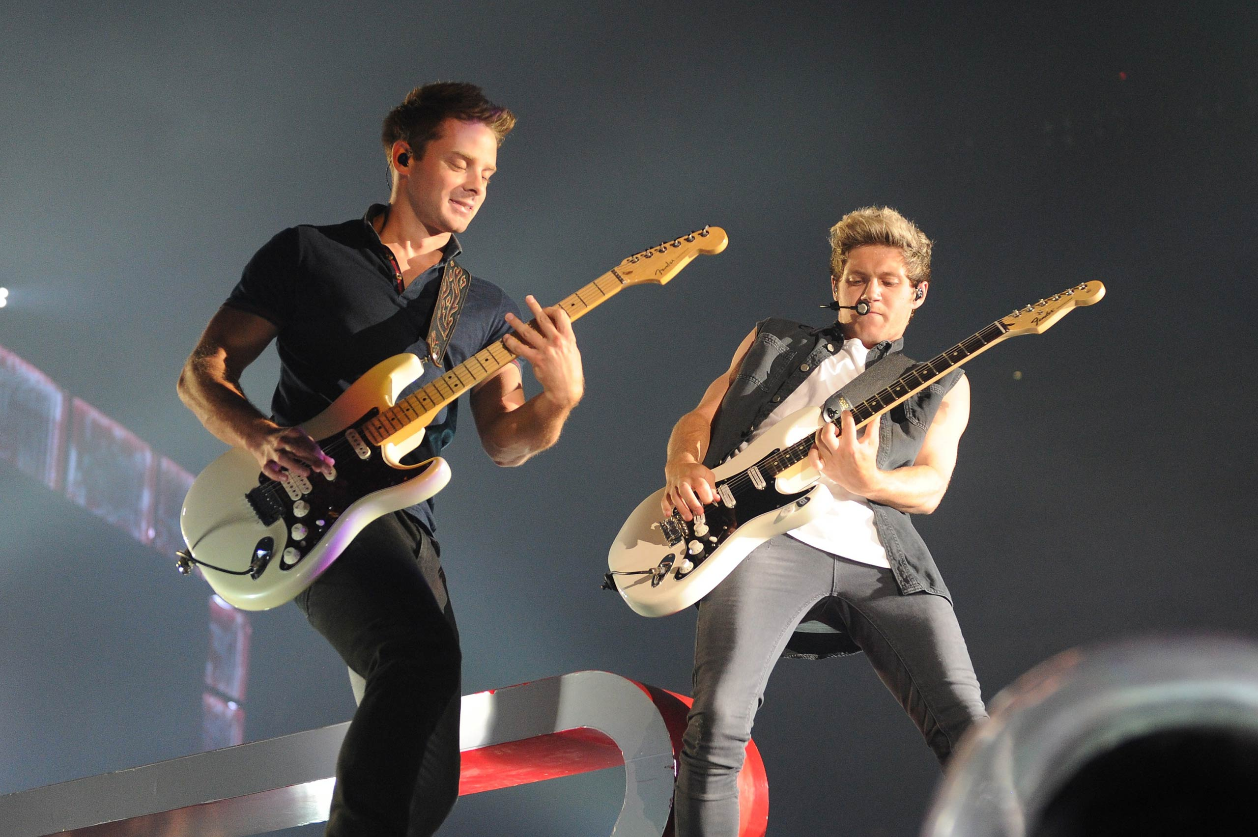 """Guitarist Dan Richards and Niall Horan of One Direction perform onstage during the """"Where We Are"""" tour at Met Life Stadium on Aug. 4, 2014 in New York City."""