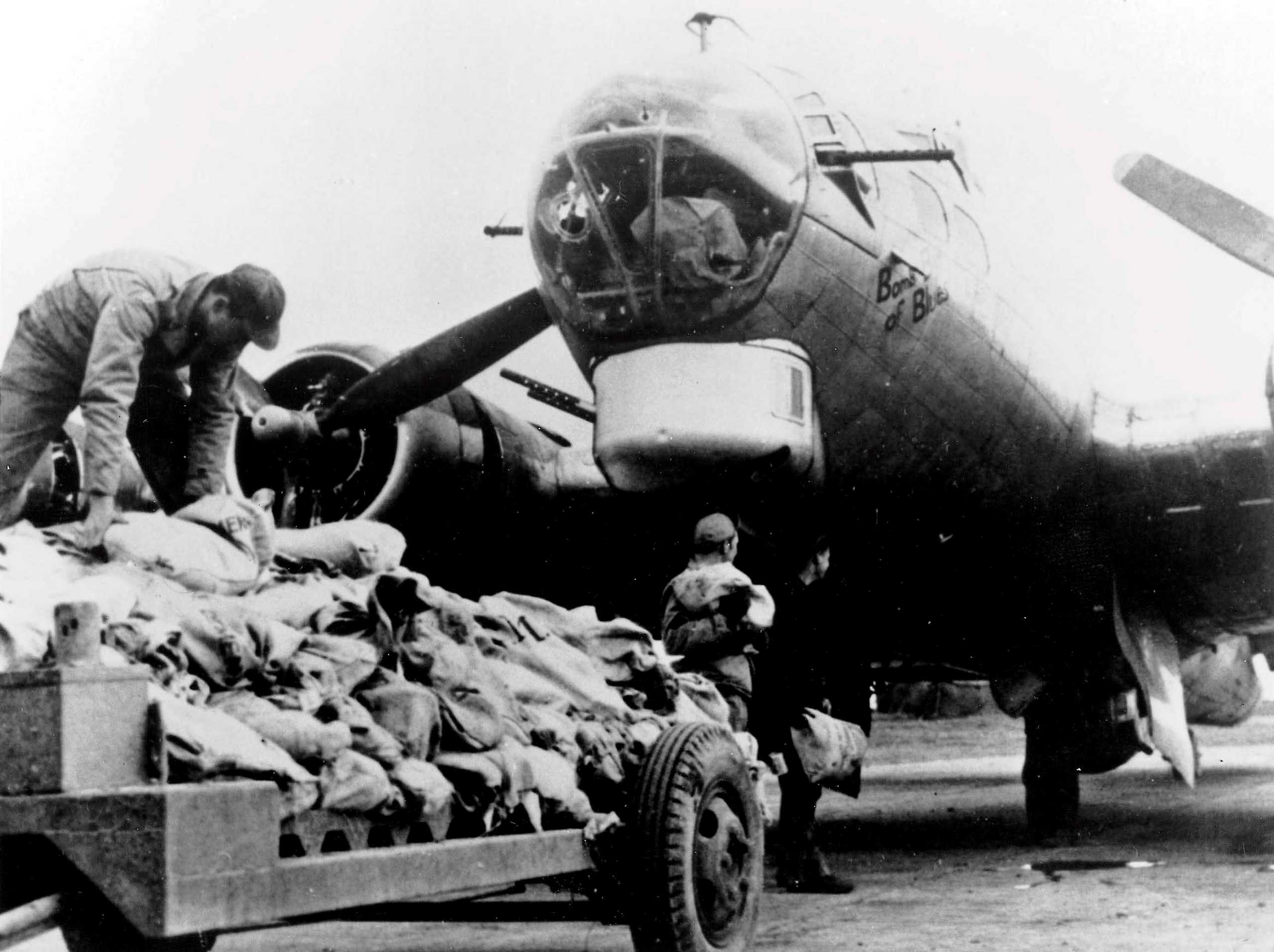 Workers load food onto an American B17 bomber during Operation Chowhound which involved dropping essential food supplies from bombers to the starving Dutch people at the end of WWII.