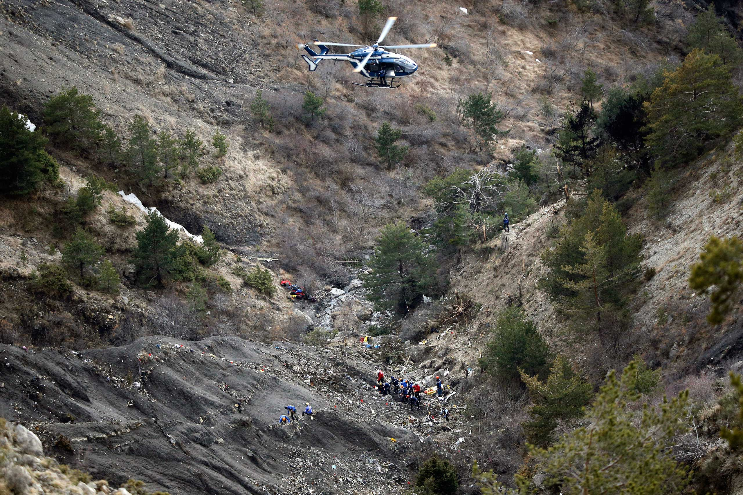 A helicopter flies overhead as rescue workers work at the crash site of Germanwings passenger plane near Seyne-les-Alpes, France, on March 26, 2015.