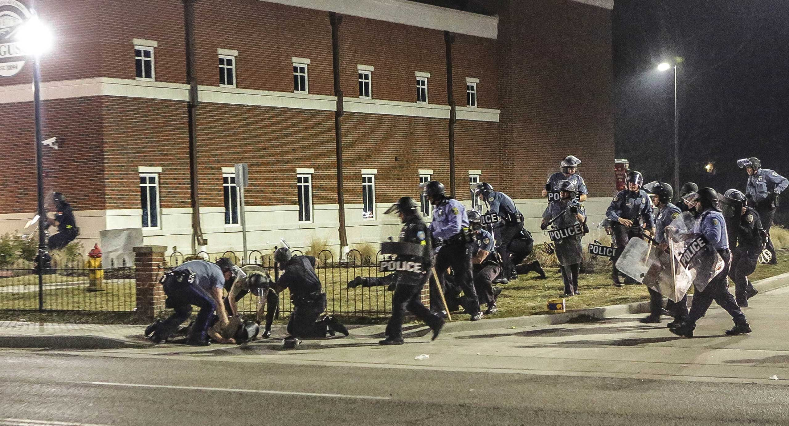 Police officers respond to a fellow officer hit by gunfire outside the Ferguson Police Headquarters in Ferguson, Mo. on March 12, 2014.