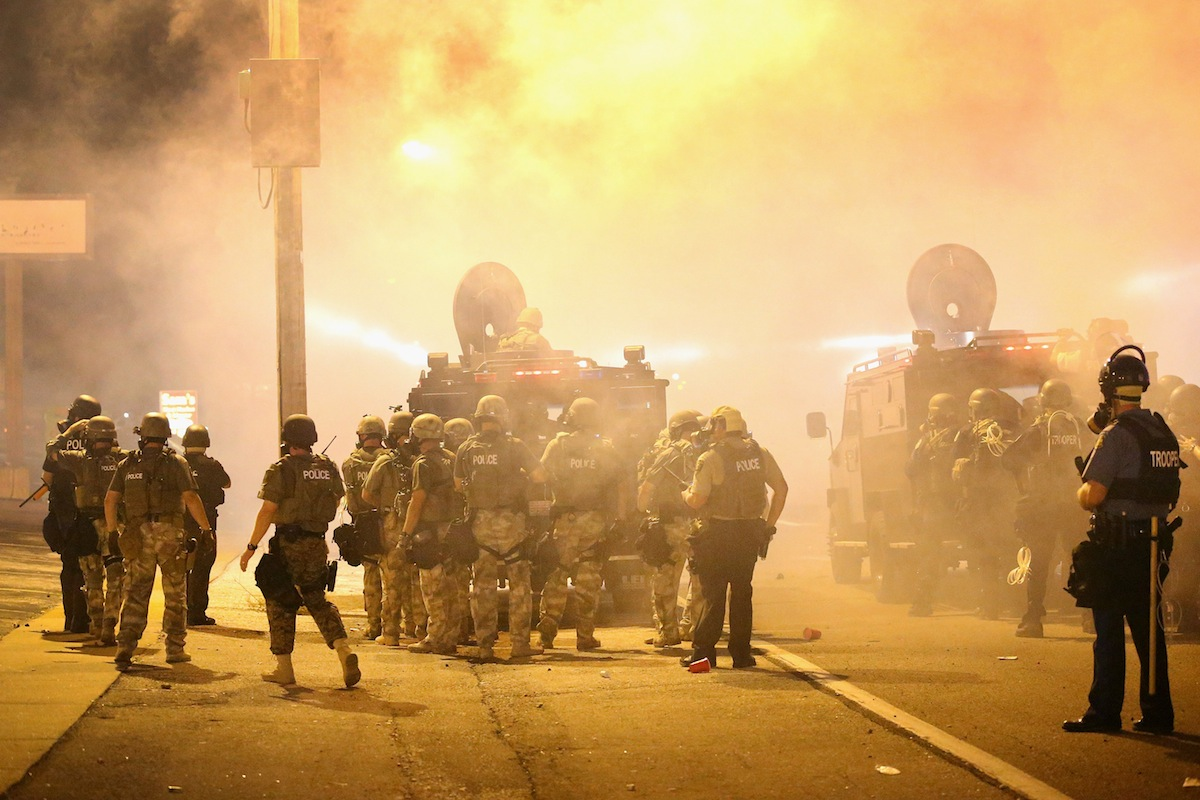 Police advance through a cloud of tear gas on Aug. 17, 2014 in Ferguson, Mo.