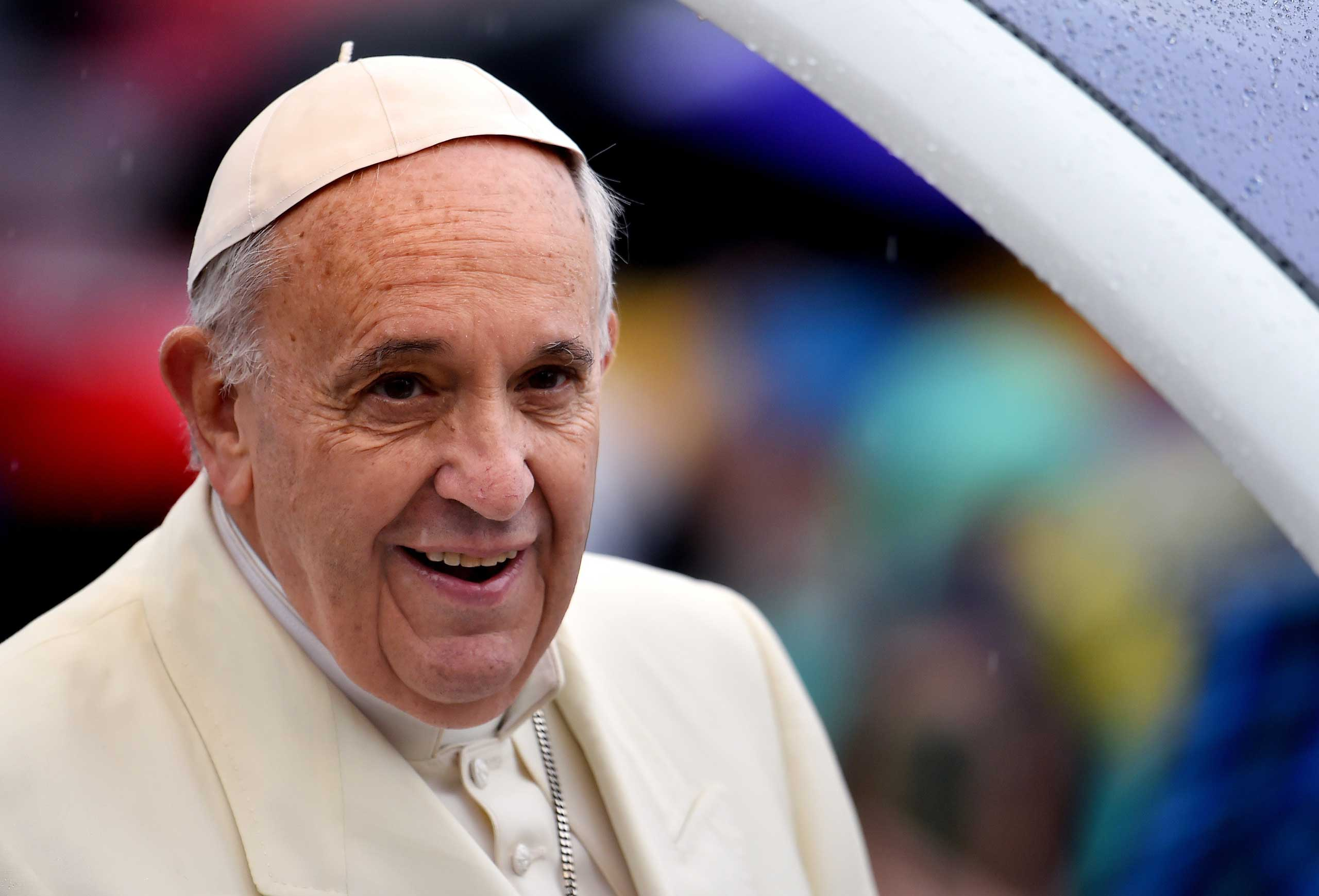 Pope Francis arrives under heavy rain, for his weekly general audience in St Peter's square at the Vatican on March 25, 2015.