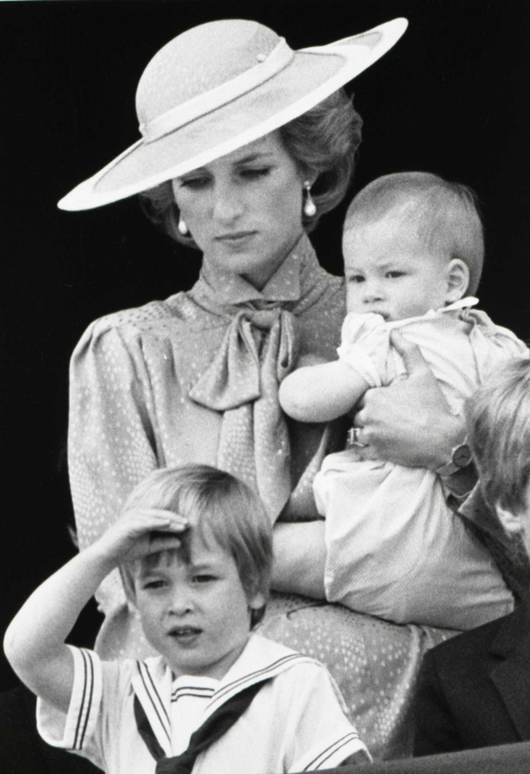 Prince Harry, aged 9 months, watches a military parade with his mother Diana, Princess of Wales, and brother William, in 1985.