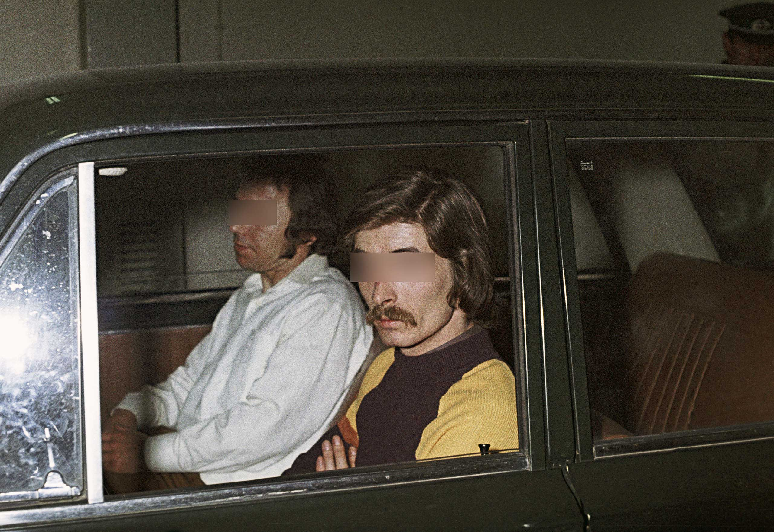 Reenactment of an escape attempt in a Fiat 124 car with Schweinfurt license plates. The attempt ended with the arrest of an escaping couple and the escape helper. The driver and front-seat passenger are reenactors. C. 1975.