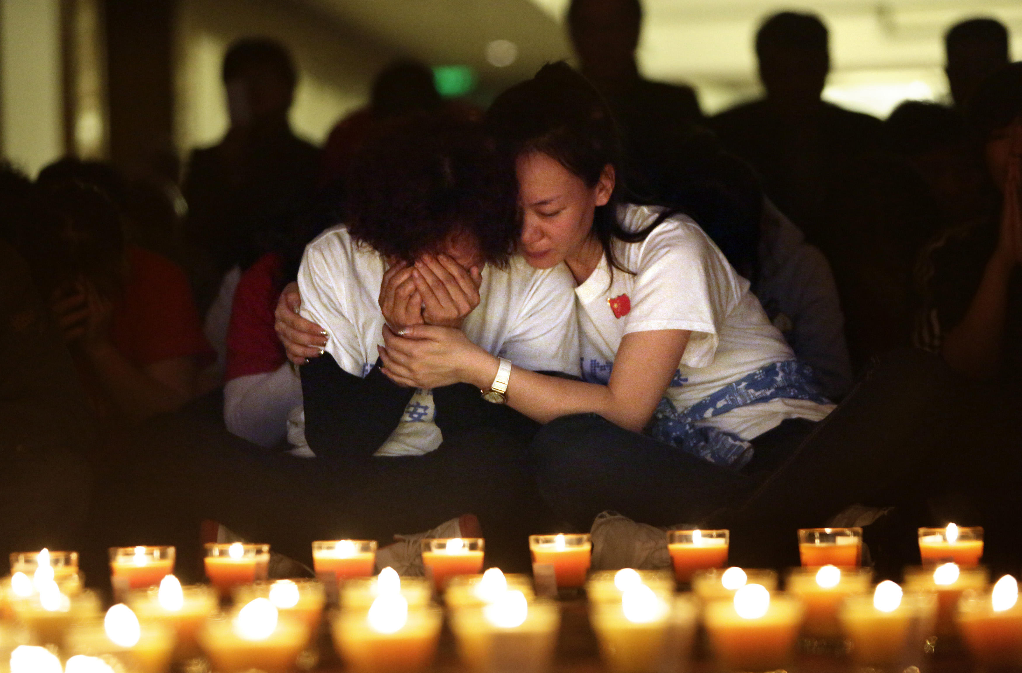 A family member cries as she and other relatives pray during a candlelight vigil for passengers aboard the missing Malaysia Airlines Flight 370 at Lido Hotel, in Beijing, on April 8, 2014, after a month of searching for the missing aircraft