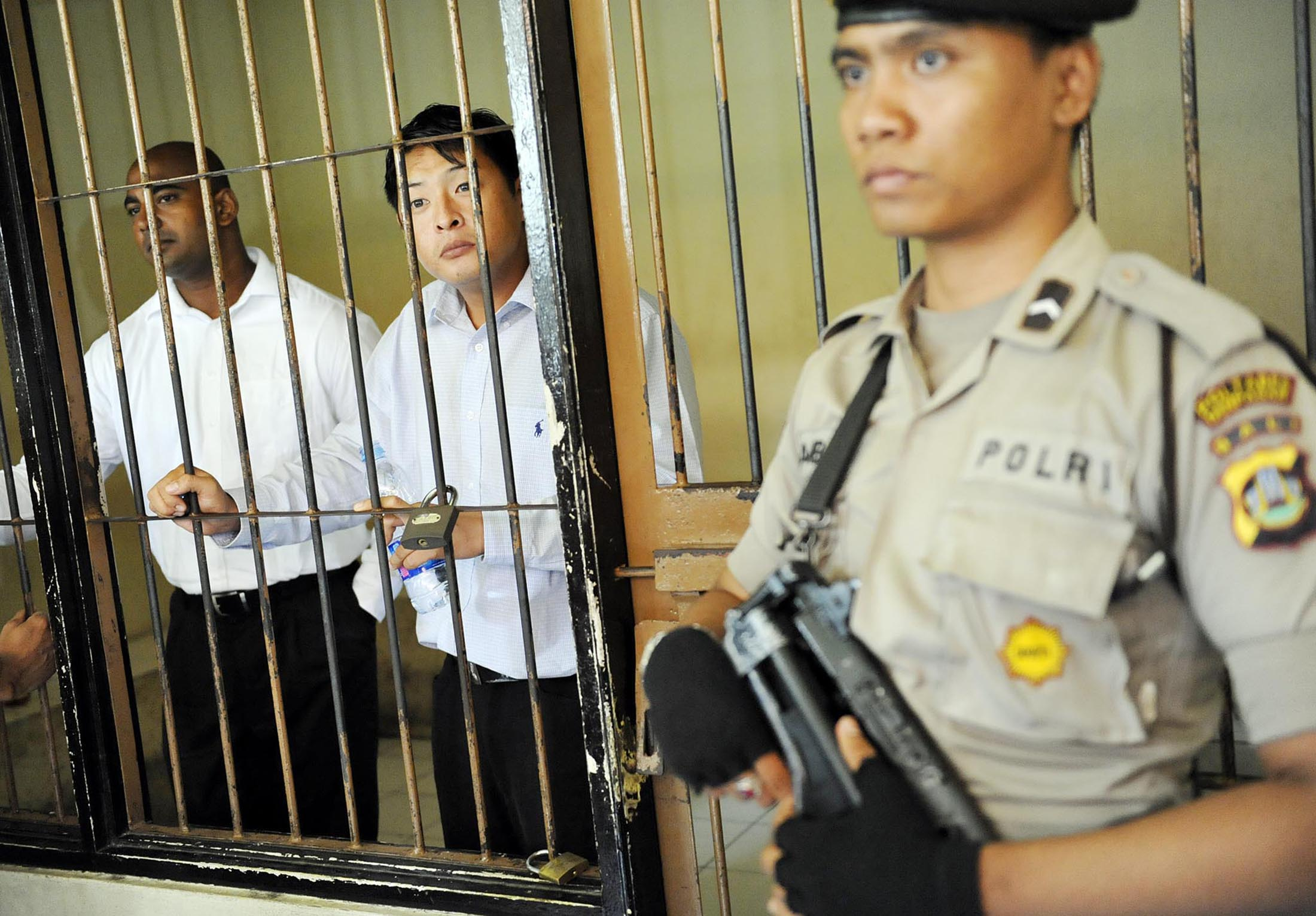 Australian death-row prisoners Andrew Chan, center, and Myuran Sukumaran, left, are seen in a holding cell waiting to attend a review hearing in the District Court of Denpasar, on the Indonesian island of Bali, on Oct. 8, 2010