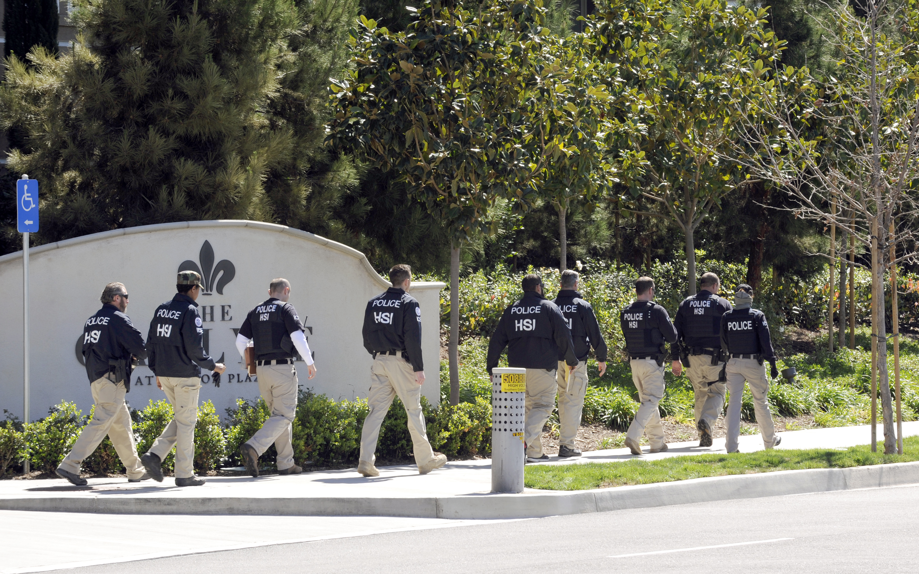 Federal agents walk past the Carlyle Apartments, the location of  a suspected  baby tourism operation,  in Irvine, Calif. on March 3, 2015.