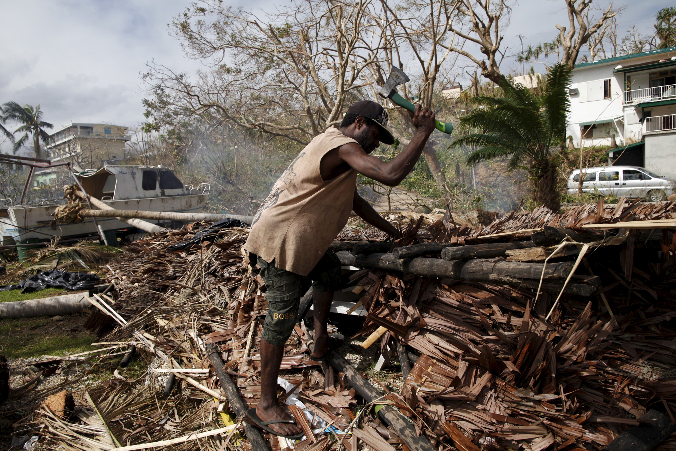 A worker chops up fallen trees next to a destroyed boat at a resident's compound days after Cyclone Pam in Port Vila, capital city of the Pacific island nation of Vanuatu March 19, 2015.