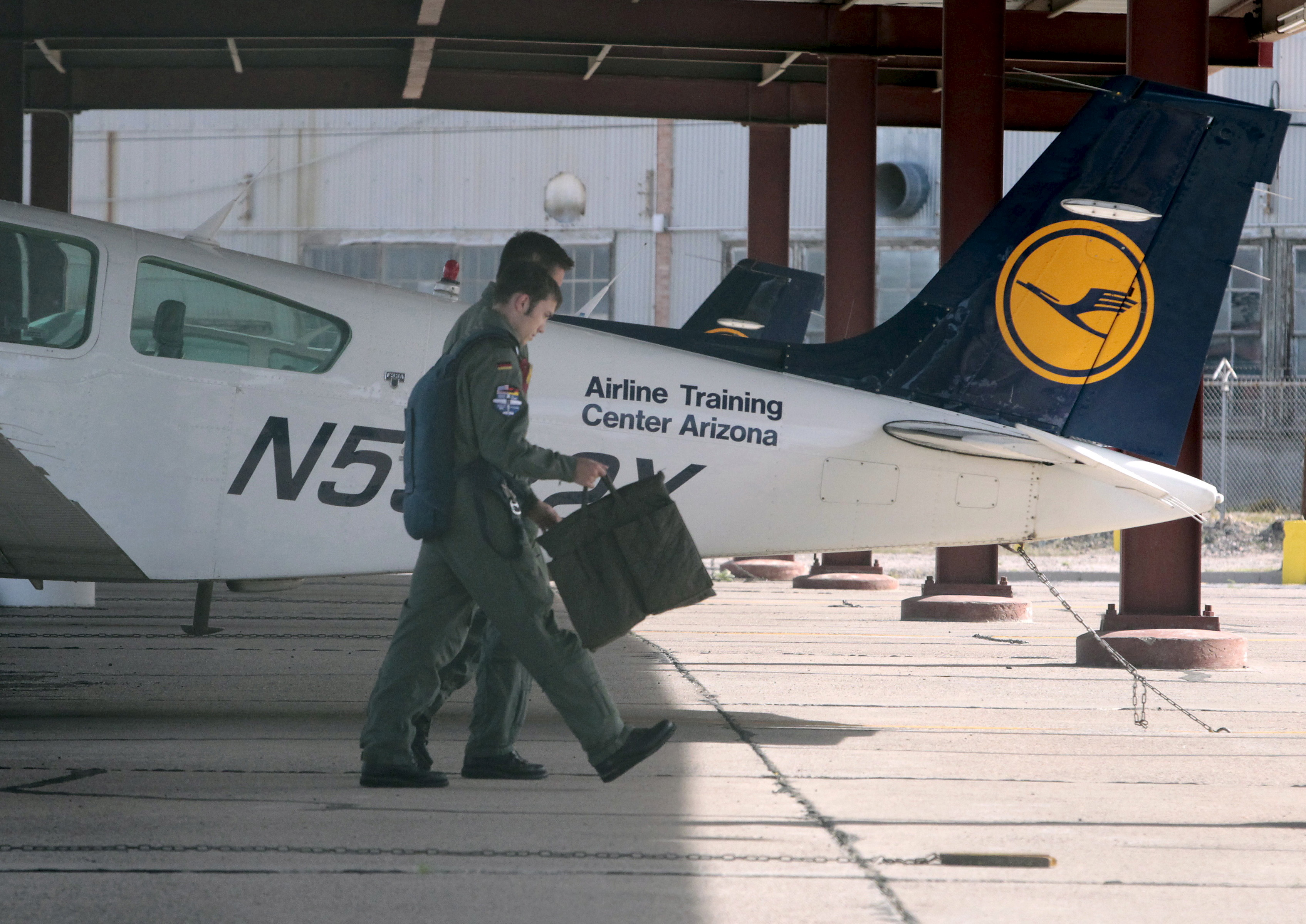 Pilots walk past a Lufthansa light aircraft trainer at the Airline Training Center Arizona (ATCA) in Goodyear, Arizona March 26, 2015