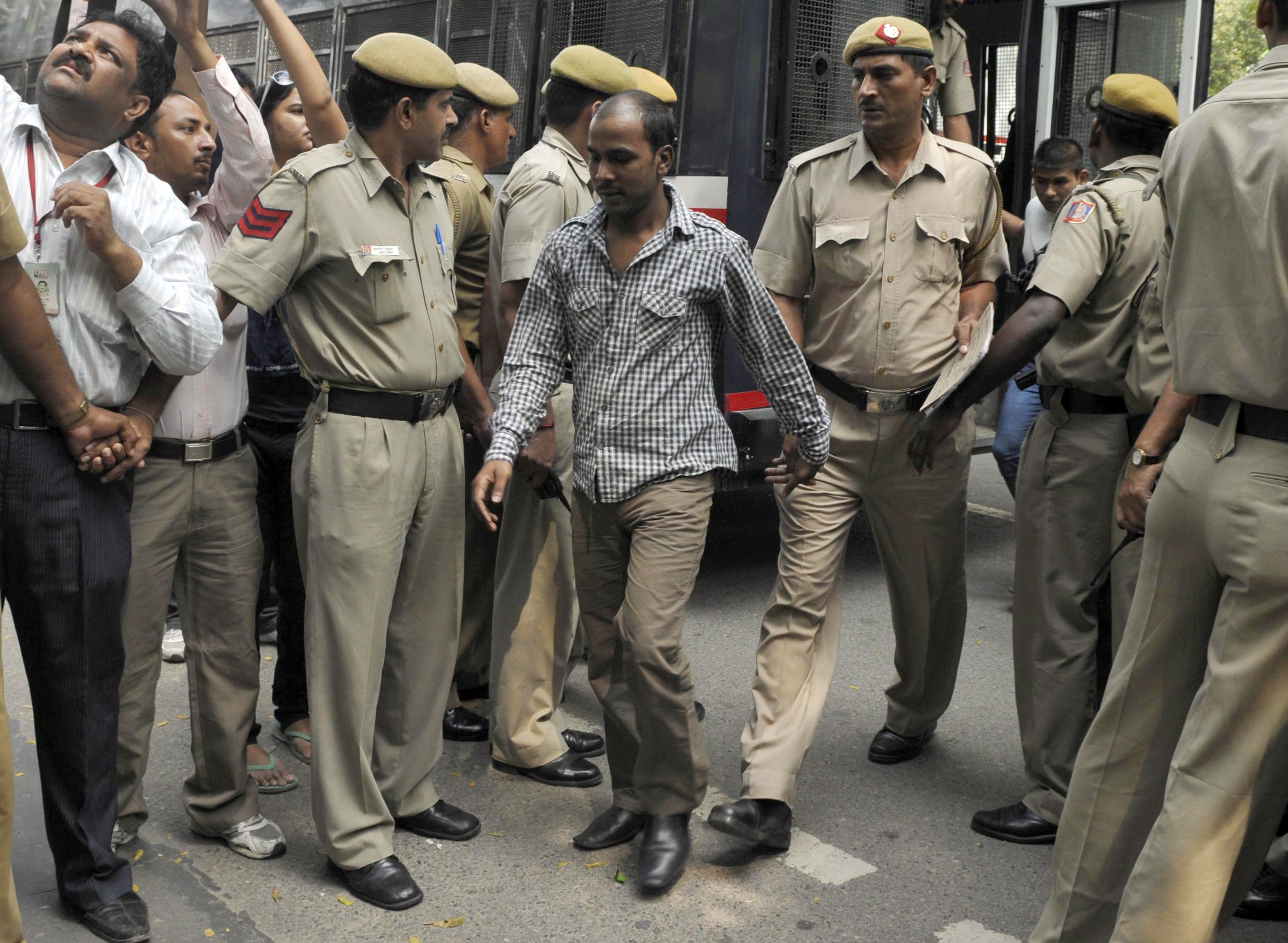 Mukesh Singh, center, one of the four men who were sentenced to death for the rape and murder of a young woman on a bus in December 2012, is escorted by police outside a court in New Delhi on Sept. 24, 2013