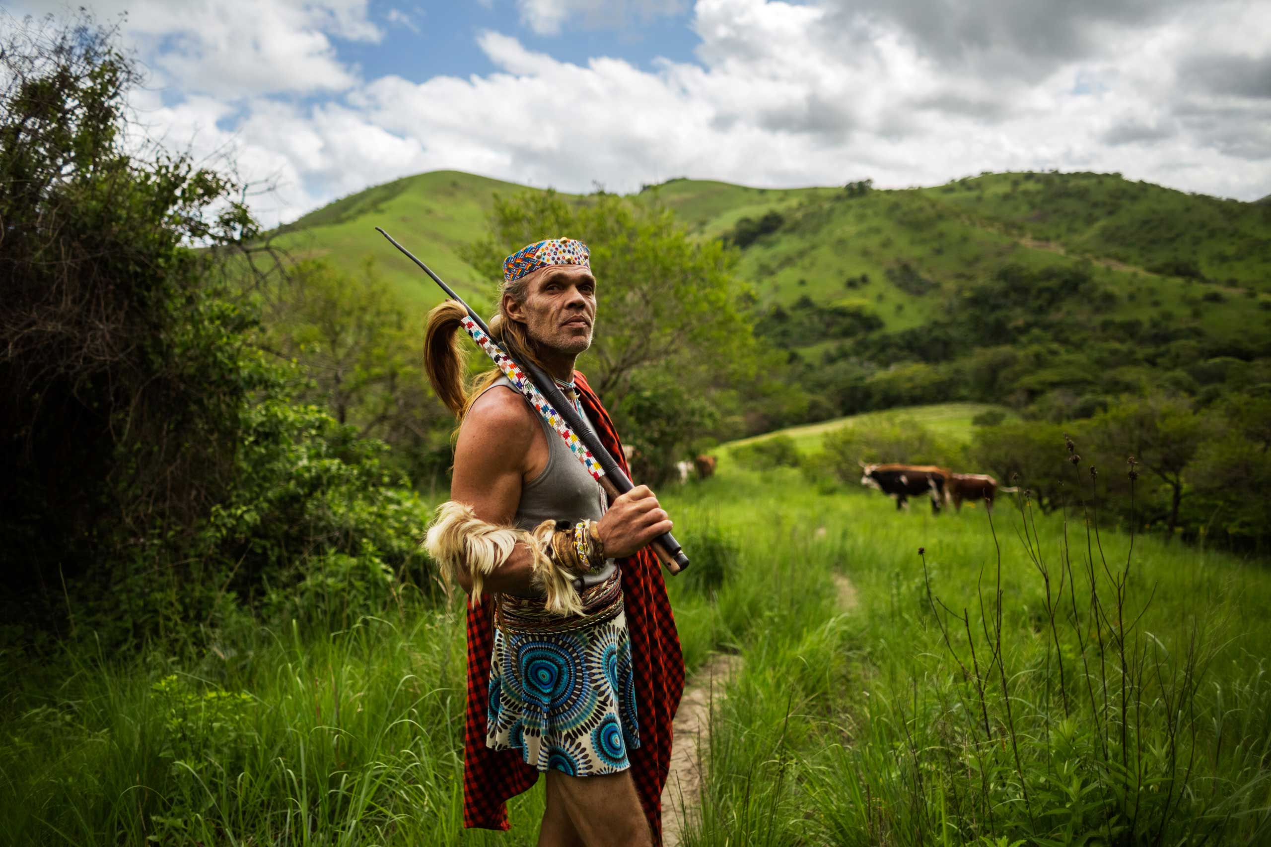 Holding his whip and itshoba (cow-tail whisk) in his hand, Chris Ntombemhlophe Reid pauses while he walks through the rural areas of the Transkei to check on his thwasa, Nolwandle, on Nov. 17, 2014 in Mdakane, Lusikisiki District, South Africa.