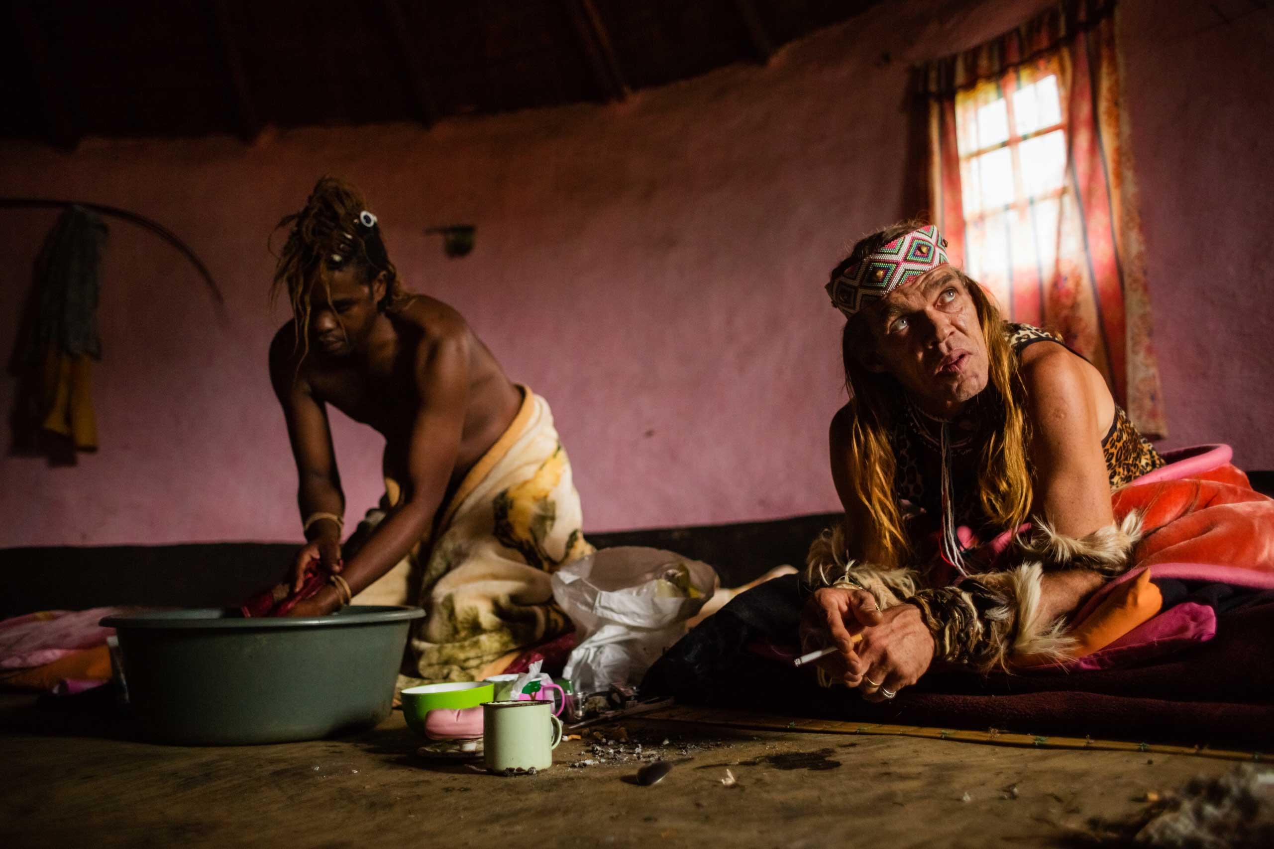 Sangoma Chris Ntombemhlophe Reid smokes a cigarette on his bed at his spiritual family's homestead while sangoma Ntombethongo washes himself on Nov. 13, 2014 in Umzizwanga, Lusikisiki District, South Africa.