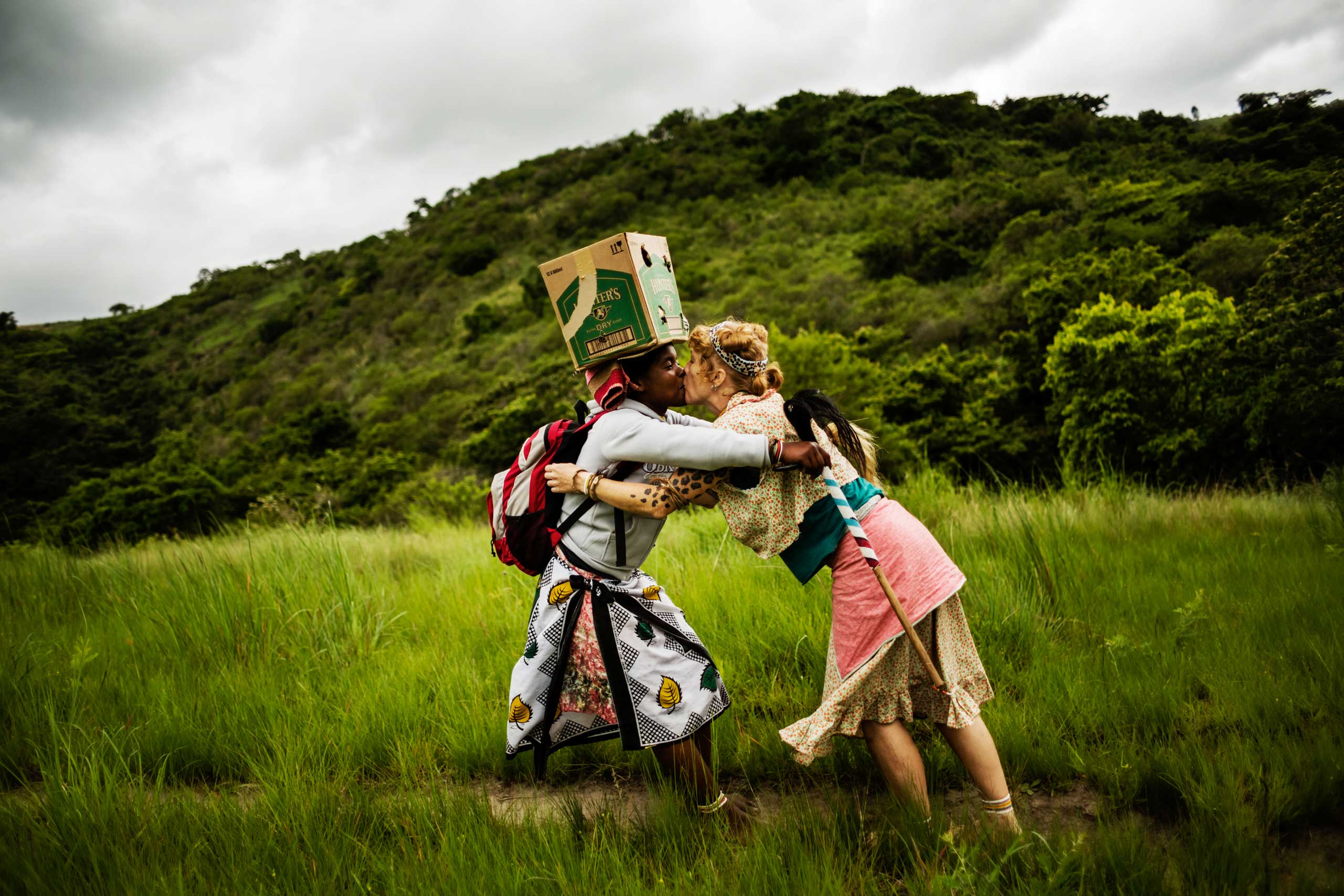 With a kiss Tyatyambo greets her spiritual sister sangoma Vumanithongo who carries a box of three chickens on her head on Nov. 20, 2014 in Mdakane, Lusikisiki District, South Africa.