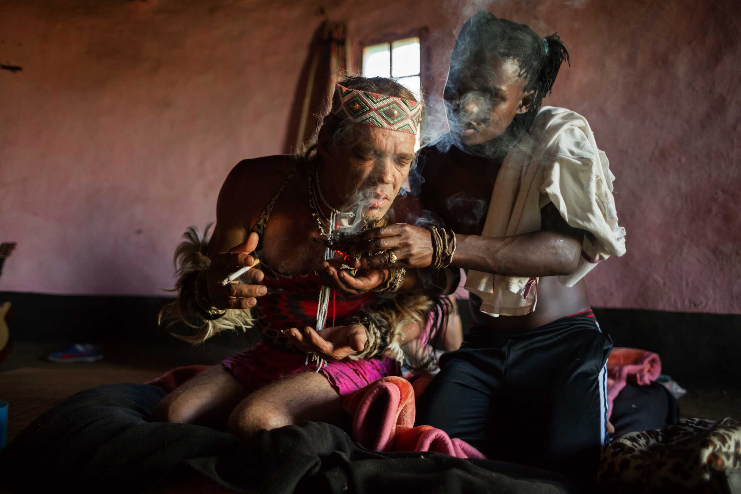 Assisted by sangoma Camagwini, Chris Ntombemhlophe Reid breathes in the smoke of burning mphepho, a herb with spiritually cleansing properties, to emotionally ground himself on Nov. 14, 2014 in Umzizwanga, Lusikisiki District, South Africa.