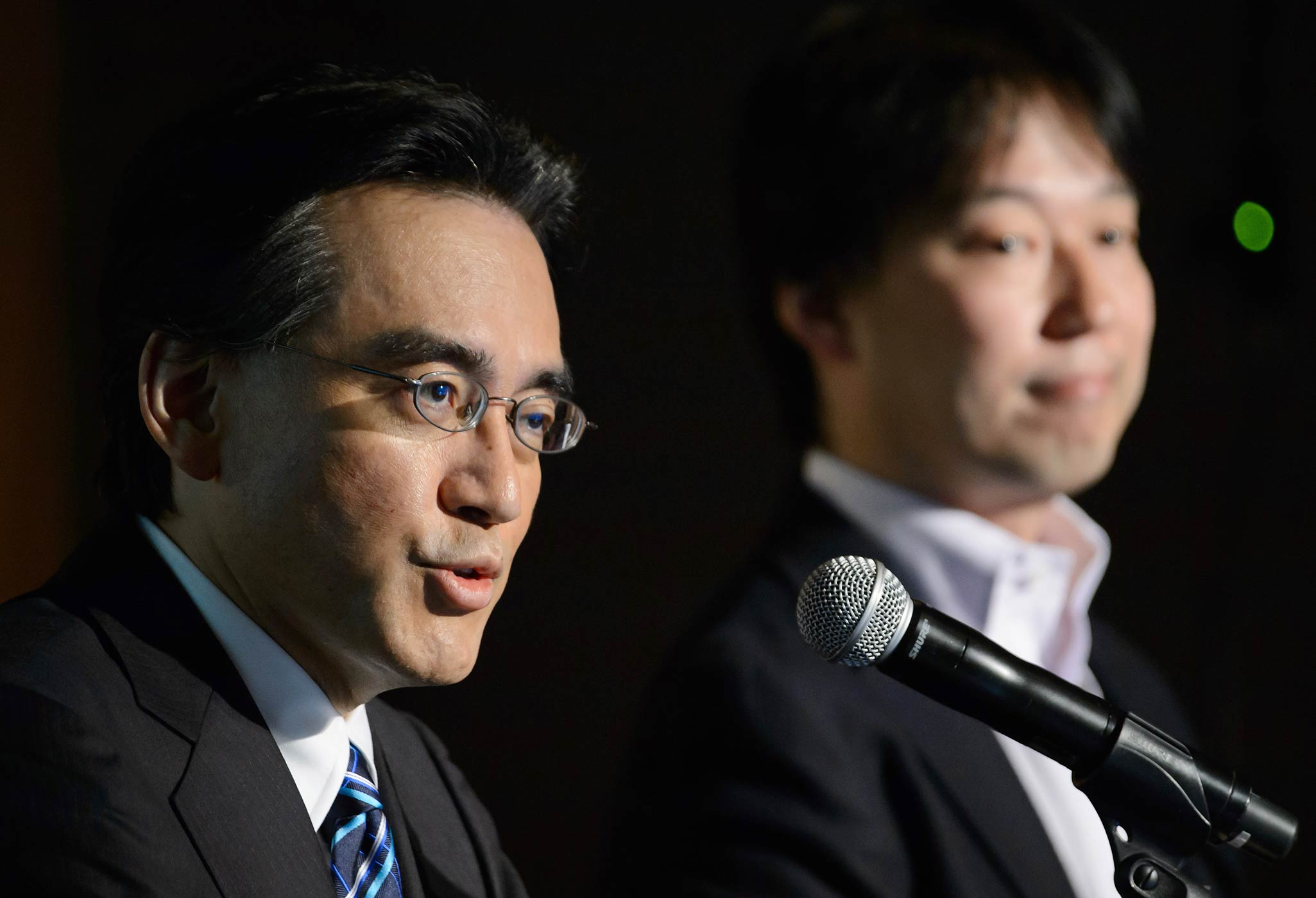 Nintendo President and CEO Satoru Iwata, left, speaks while DeNA Co. President and CEO Isao Moriyasu listens during a joint news conference in Tokyo, Japan, on March 17, 2015.