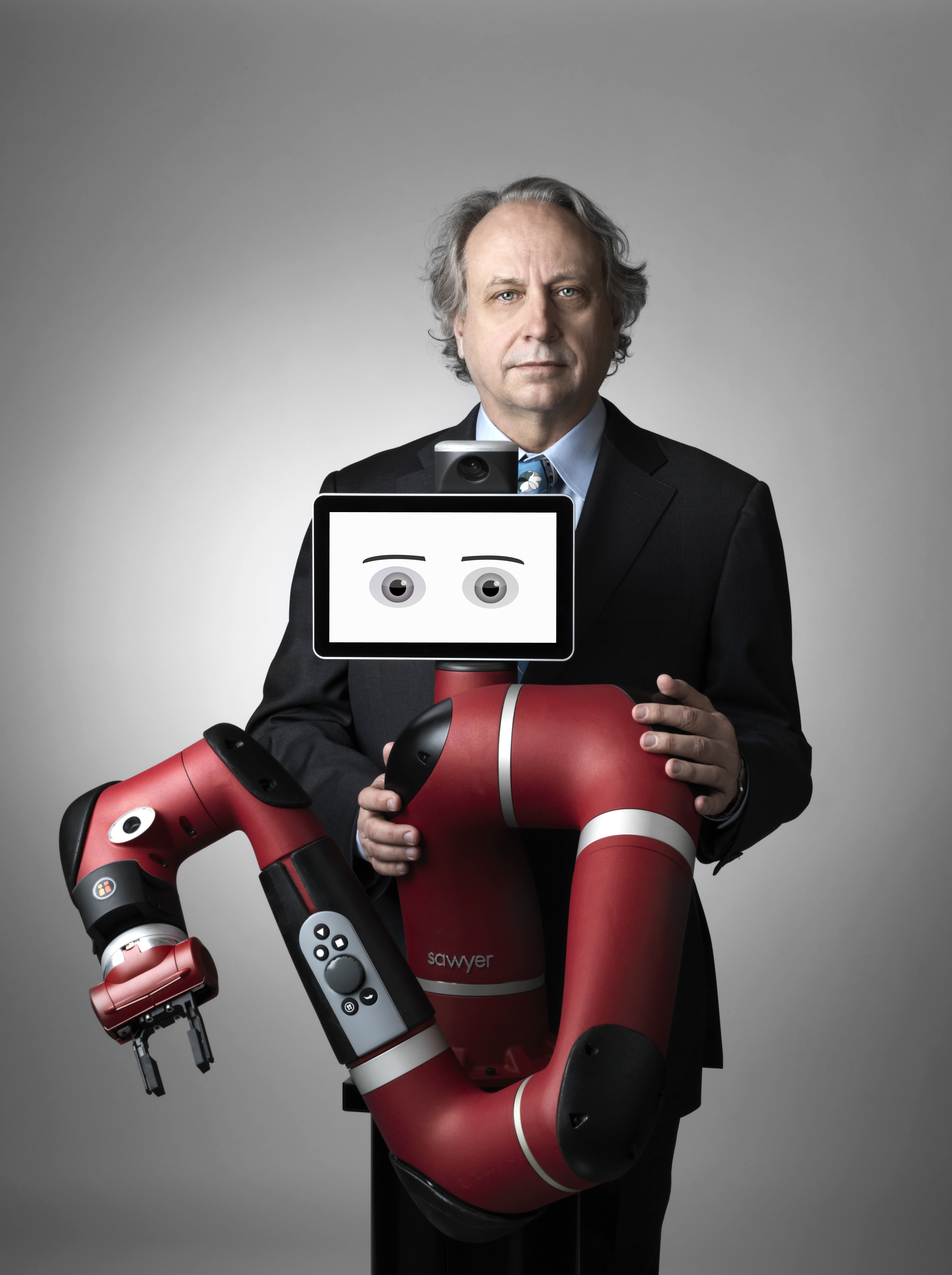 Rethink Robotics co-founder Rodney Brooks poses with Sawyer, the company's newest smart, collaborative robot.