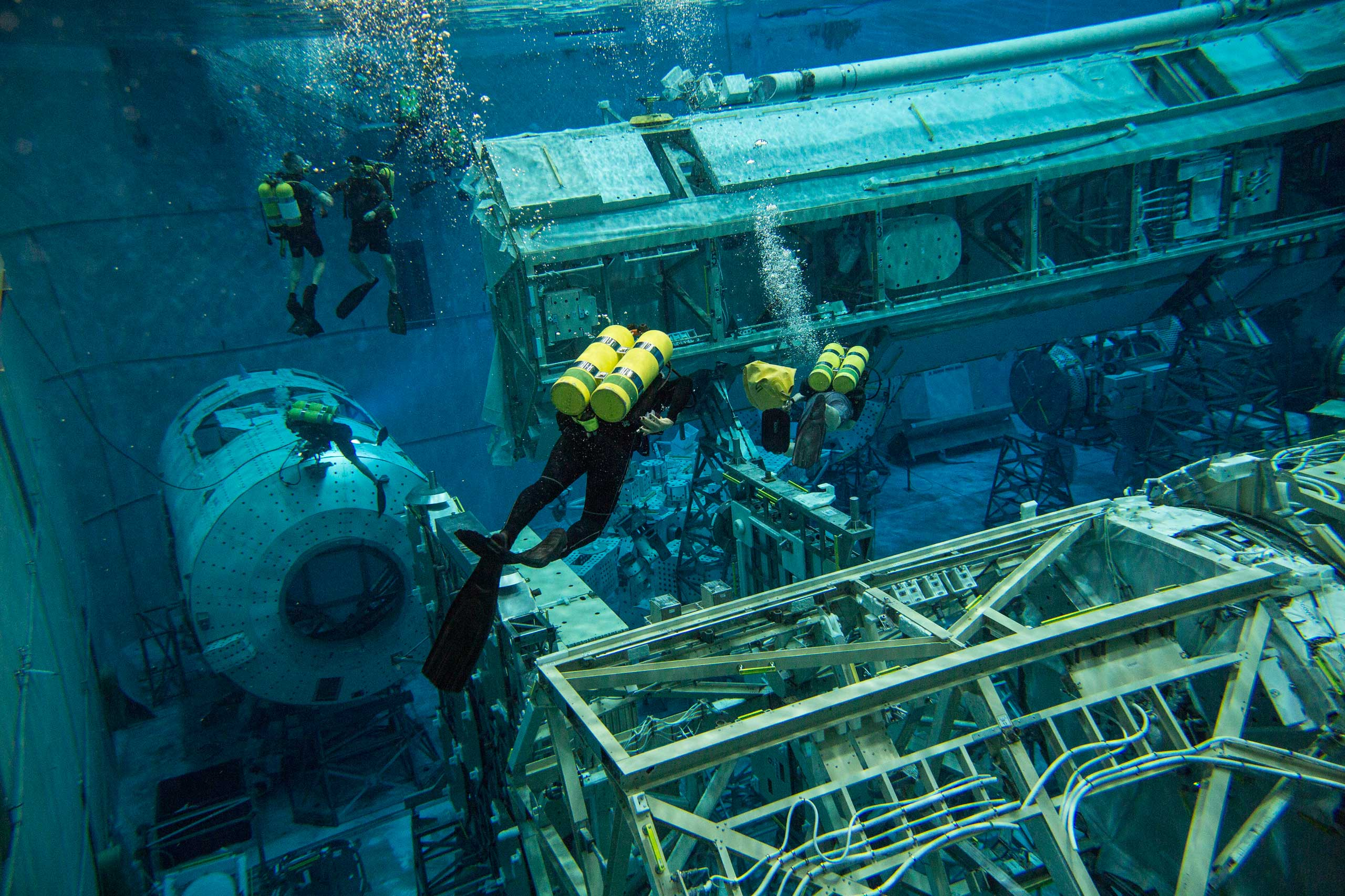 Divers swim toward an underwater replica of the International Space Station in Houston on Feb 3, 2015. Astronauts train for spacewalks by wearing their spacesuit in the world's largest pool, at NASA's Neutral Buoyancy Lab in Houston.